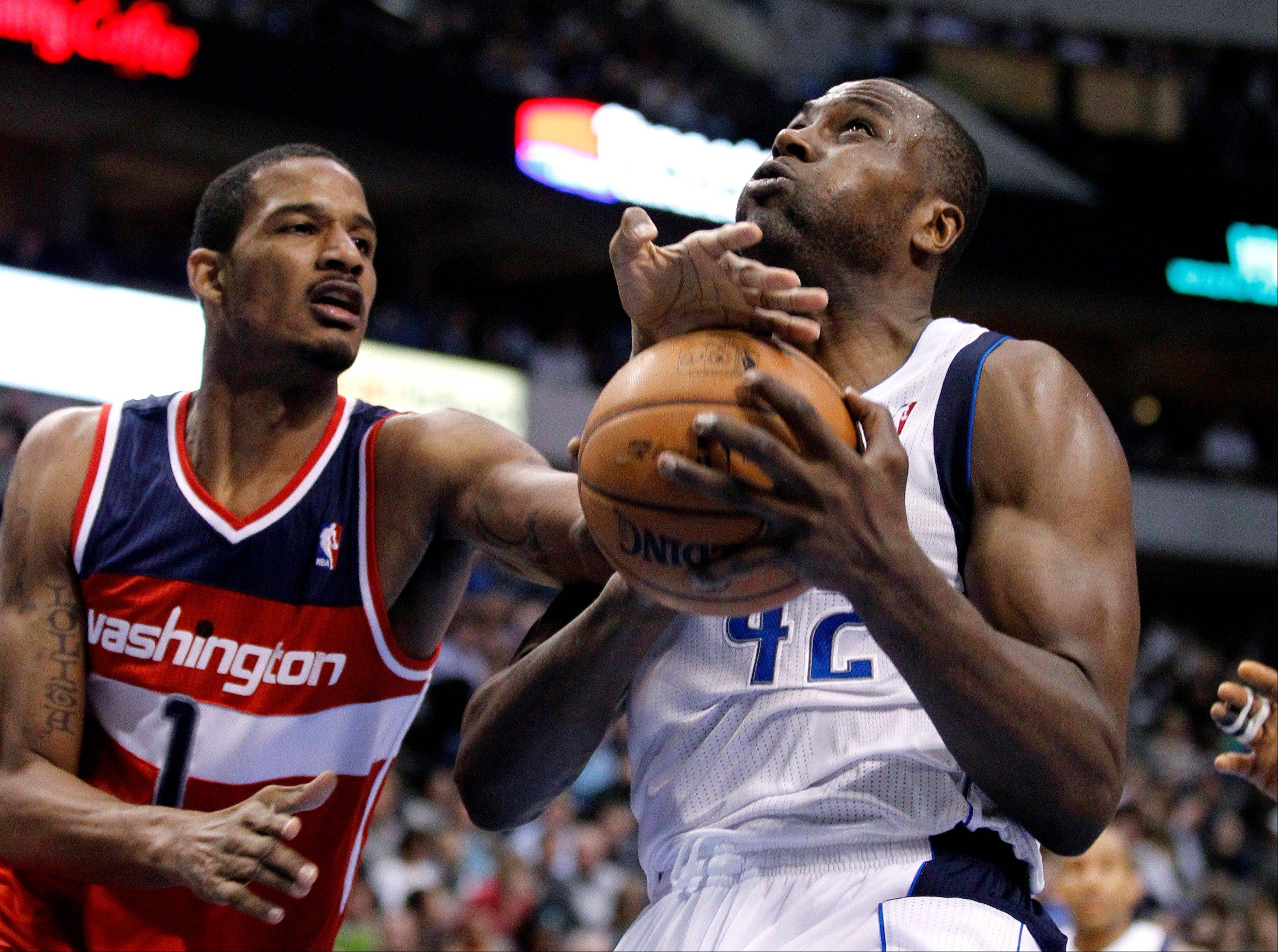 The Washington Wizards' Trevor Ariza stops a drive to the basket by the Dallas Mavericks' Elton Brand Wednesday during the second half in Dallas. The Mavericks won 107-101.