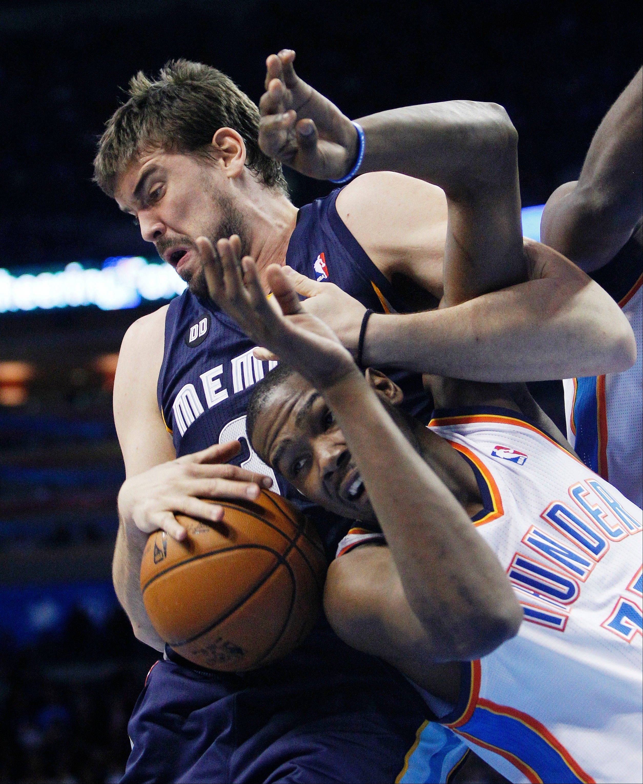 Memphis Grizzlies center Marc Gasol, left, wraps up Oklahoma City Thunder forward Kevin Durant, right, as he grabs a rebound Wednesday during the second quarter in Oklahoma City.