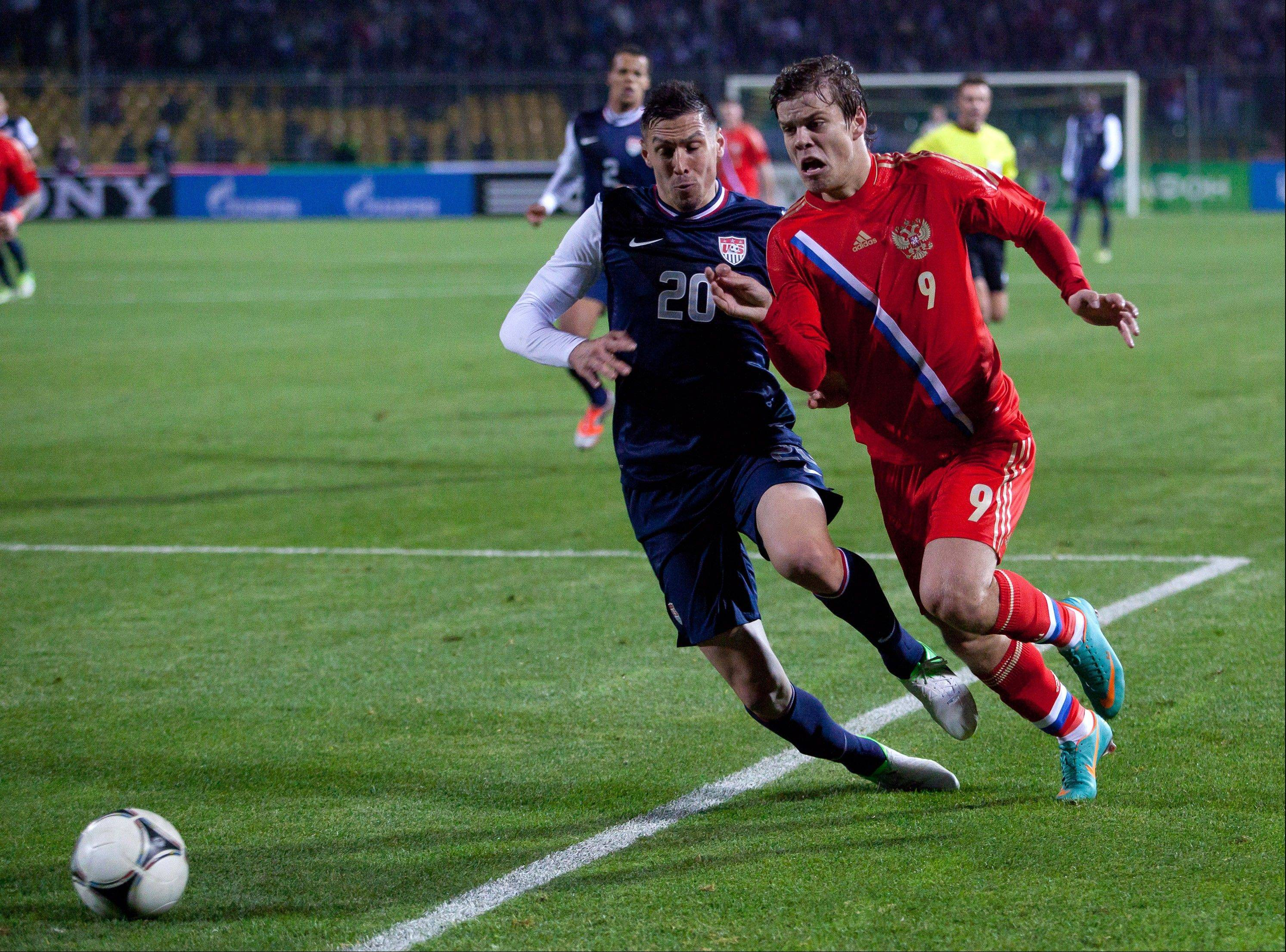 Alexander Kokorin, of Russia, right, and Geoff Cameron, of the United States, struggle for the ball Wednesday during a friendly between Russia and United States, in Krasnodar, Russia. The game ended in a 2-2 draw.