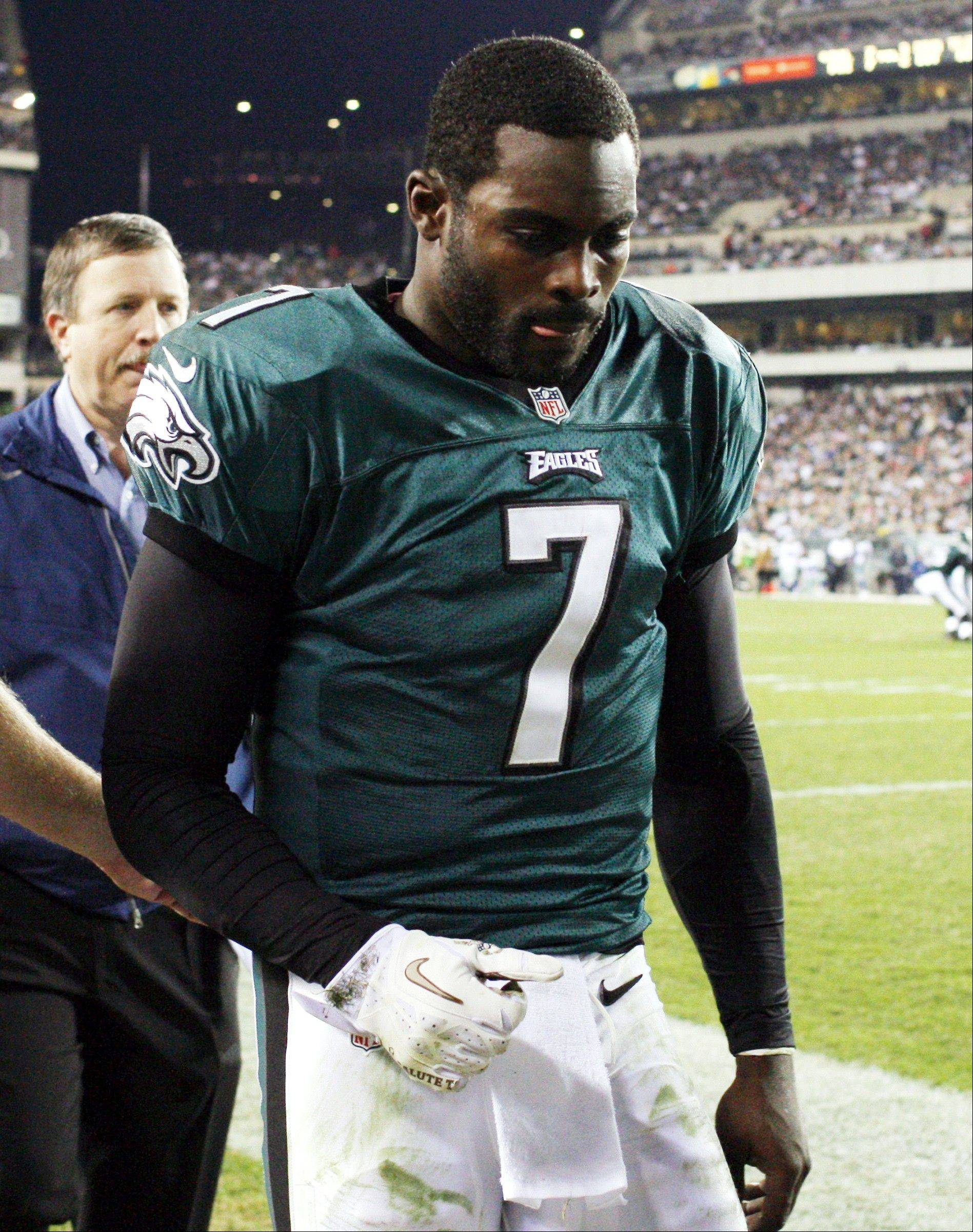 Philadelphia Eagles quarterback Michael Vick leaves the field after suffering a concussion Sunday during the second quarter against the Dallas Cowboys in Philadelphia. Vick has not been ruled out for Sunday's game against Washington.