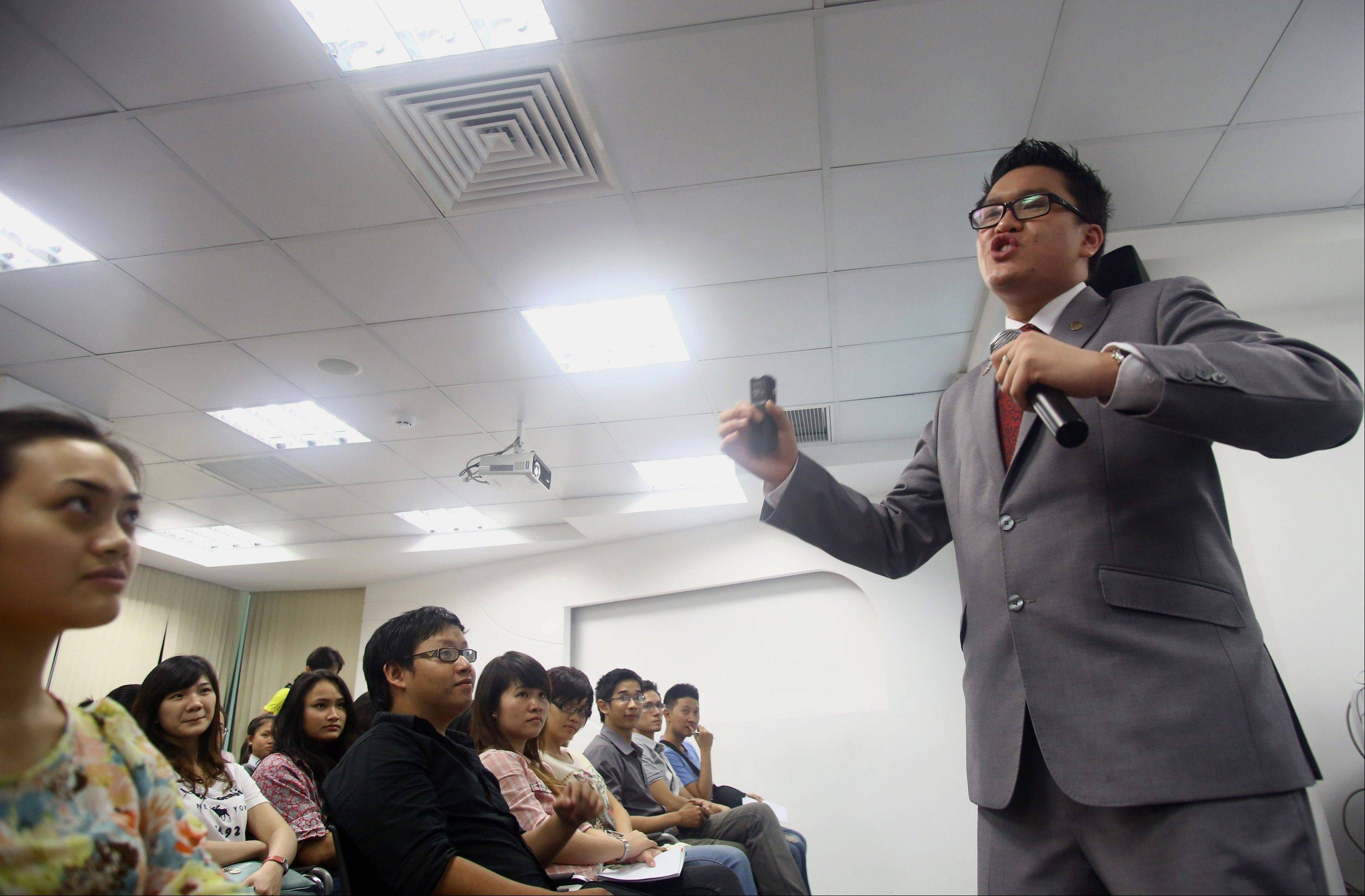 Australian Brian Tan, right, a �blue diamond� sales executive of Nu Skin, a multilevel marketing company, speaks during a presentation to economic students to expand and recruit distributors for his sales system at Nu Skin�s office in Ho Chi Minh City, Vietnam. Nu Skin, which has stormed through Asia over the last two decades, racked up huge profits despite regulatory scrutiny over its marketing practices and the efficacy of the products that it sells.