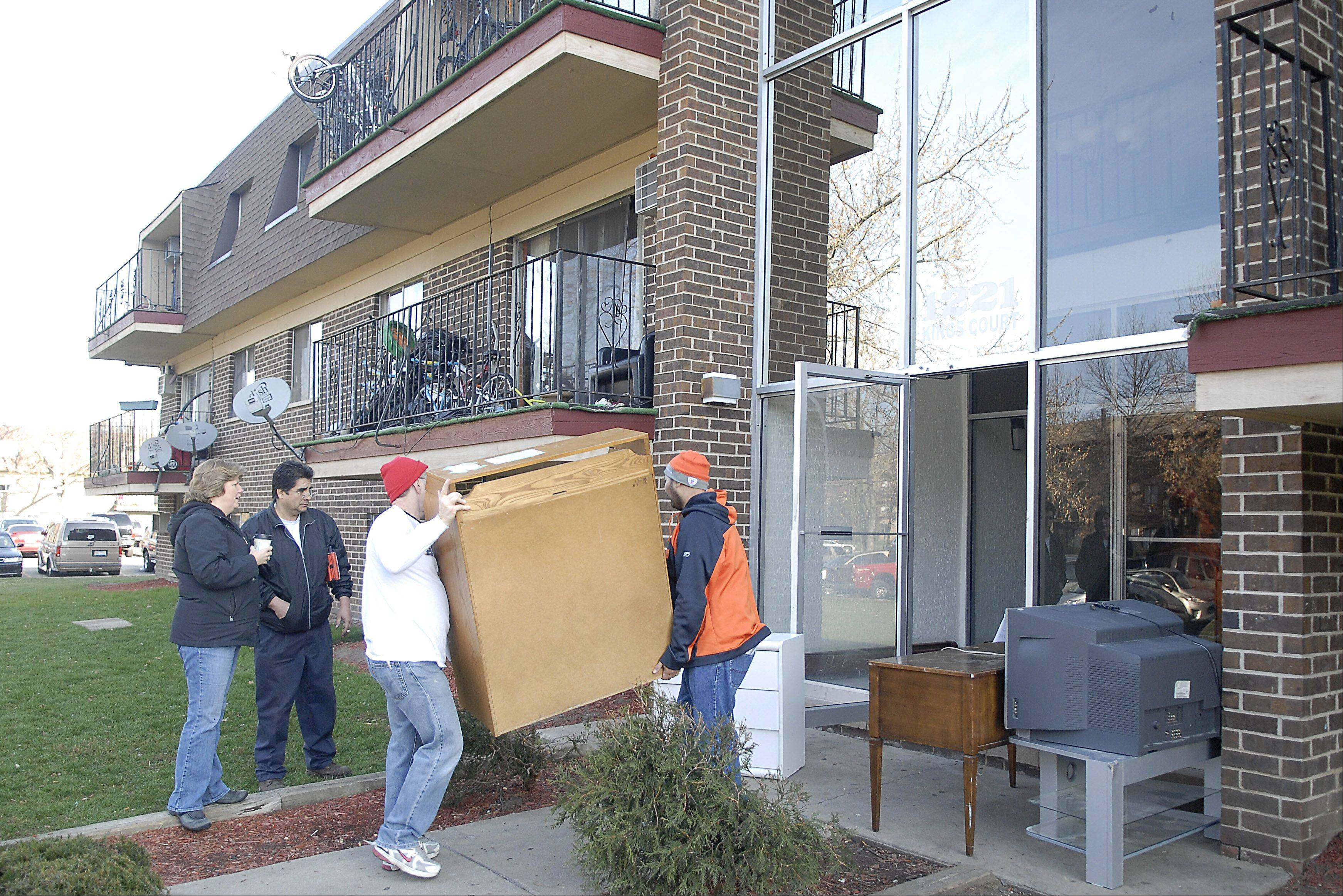 Vanessa Roth of Puenta del Pueblo talks with Timber Lakes resident Jose Rodriguez while volunteers Chuck Sahly of Winfield and Norberto Camargo of Bartlett move new furniture into the apartment of one of eight families who were living in the apartments damaged by a fire Nov. 4. Rodriguez lost his belongings in the fire and was waiting for his delivery � but also was ready to help out.