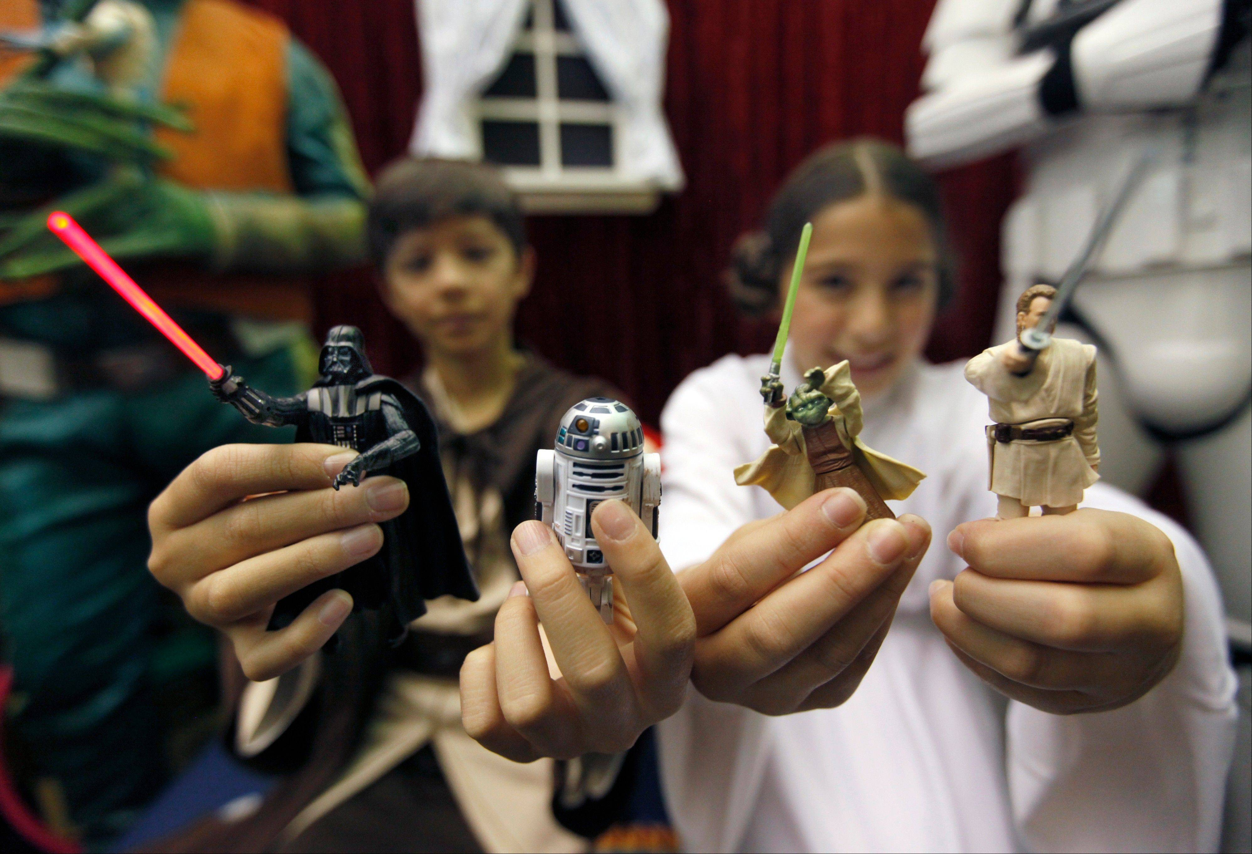 Chase Boss, left, 11, as Luke Skywalker and his twin sister Sydney as Princess Leia hold Star Wars action figures, which were inducted into the National Toy Hall of Fame at The Strong in Rochester, N.Y., Thursday.
