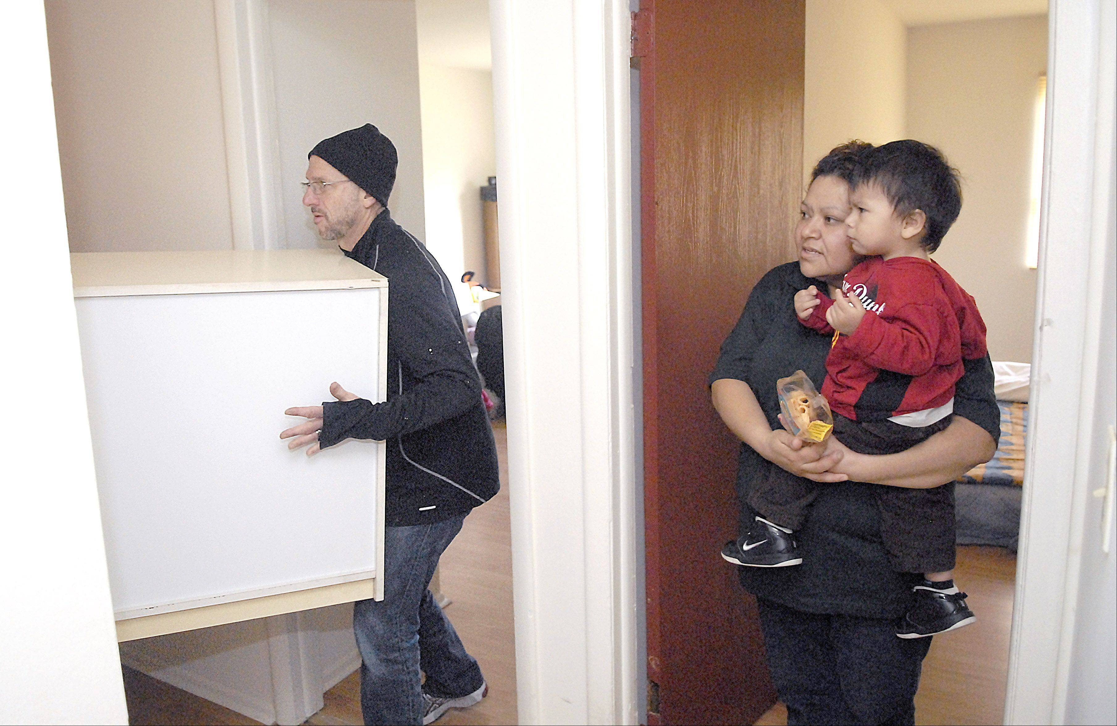 Juana Beltran holds her son, Alexis, 2, and watches as the Rev. Jeff Walser of Wheaton Bible Church helps move furniture into her apartment at the Timber Lakes complex in West Chicago on Saturday. Eight families were living in the apartments damaged by a fire on Nov. 4. Community Outreach Ministries and Wheaton Bible Church worked with the West Chicago community to gather and fund the replacement furniture.