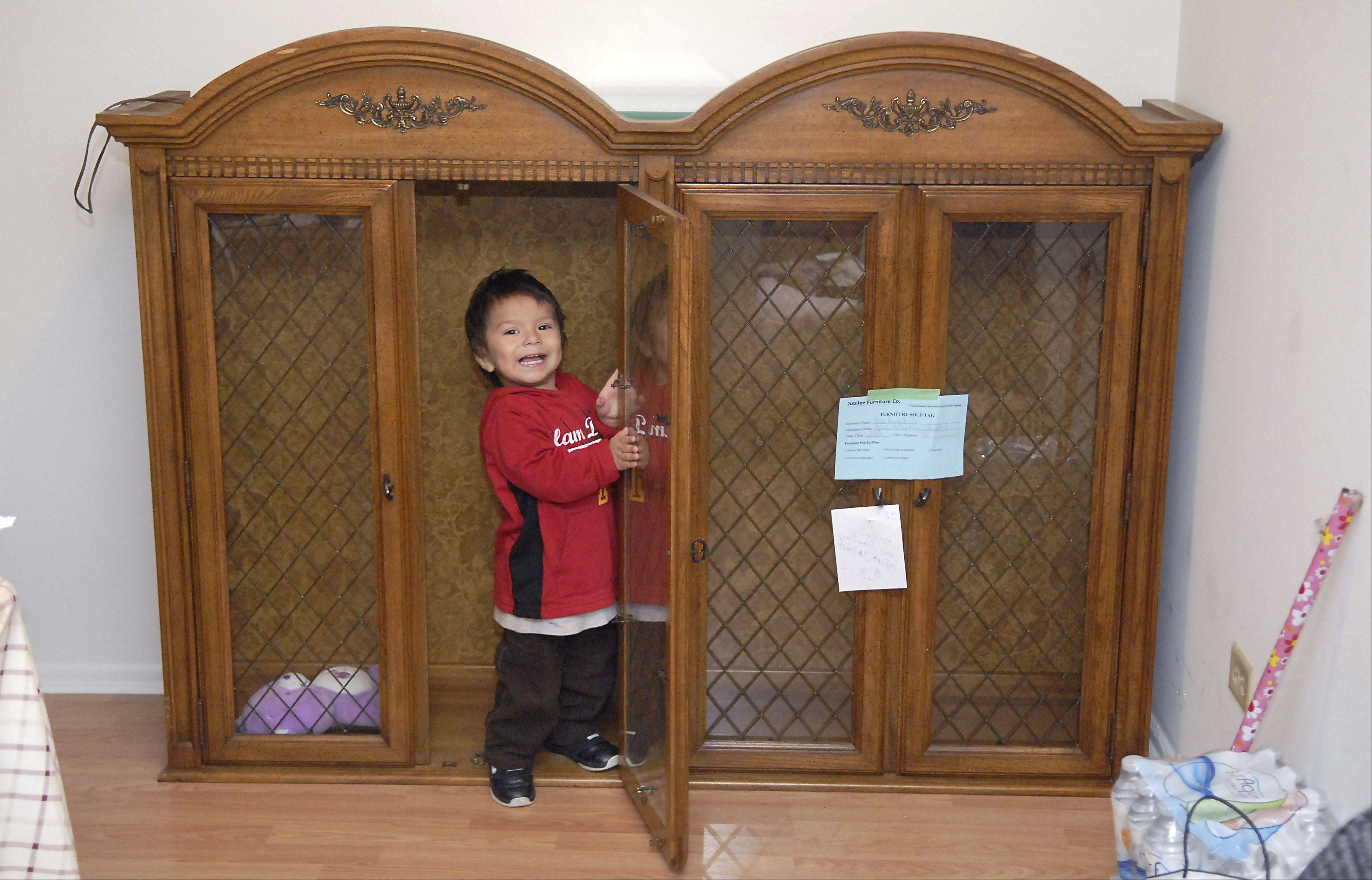 Alexis Rangel, 2, plays in top part of a new curio cabinet delivered to his parents, Juana Beltran and Jose Rangel, on Saturday. They were one of eight families living in the apartments damaged by fire on Nov. 4. Community Outreach Ministries and Wheaton Bible Church worked with the West Chicago community to gather and fund the replacement furniture.