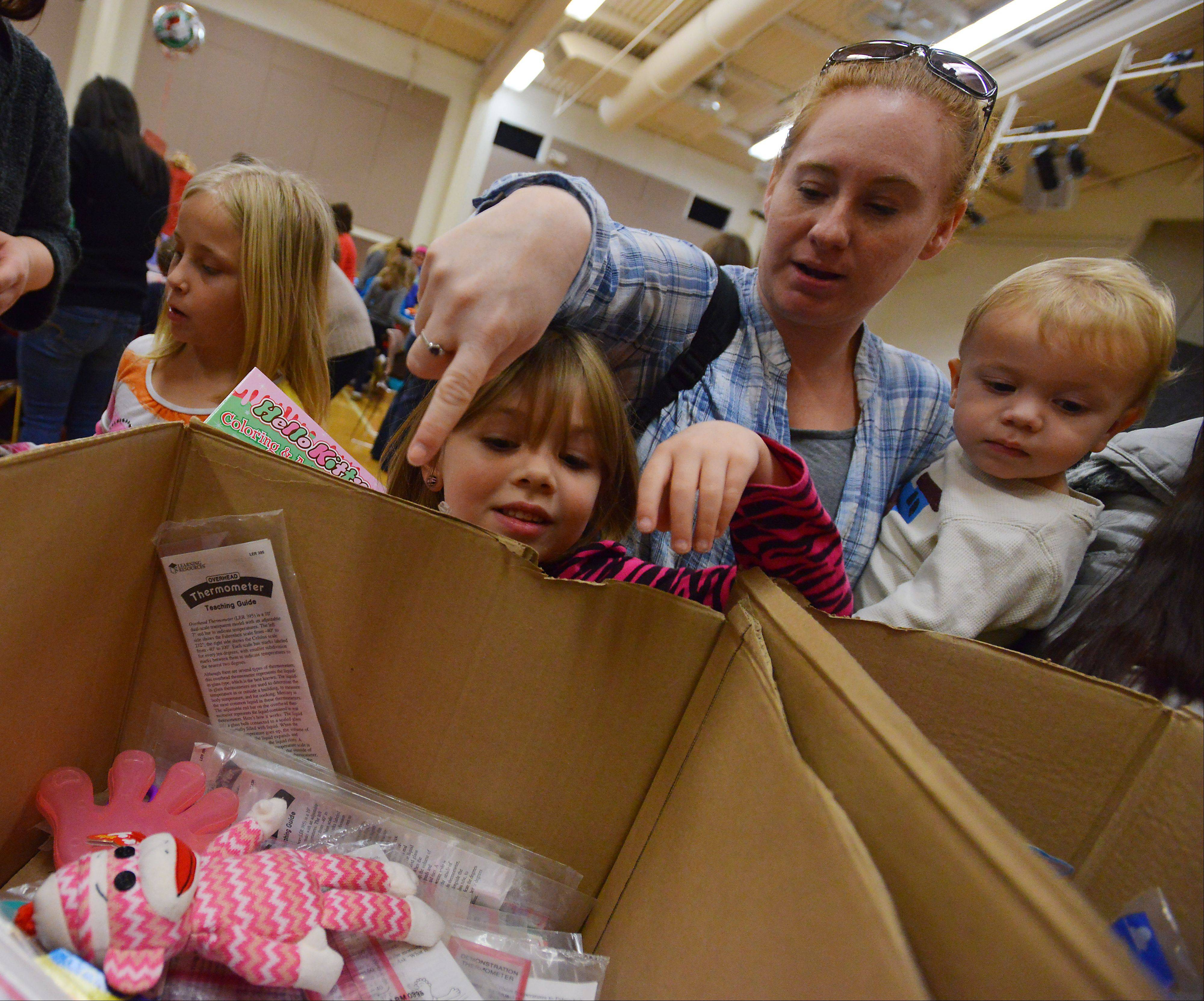 Miranda Jones, 5, of Round Lake picks out gift items to pack in a shoe box Saturday with her 2-year-old brother, Shane, and her mom, Melissa Jones. The family packed gift boxes to be sent overseas to children in need as part of Operation Christmas Child at Immanuel Church in Gurnee.