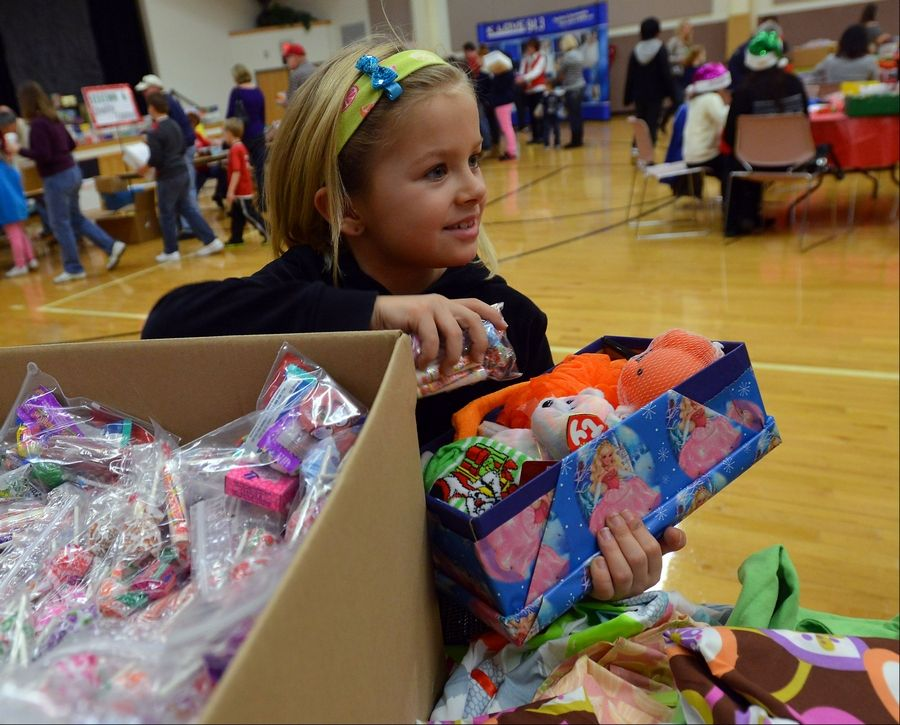 Olivia Spillman, 7, of Gurnee, packs a shoe box Saturday with stuffed animals, candy and other fun items that will be sent to needy children overseas as part of Operation Christmas Child.