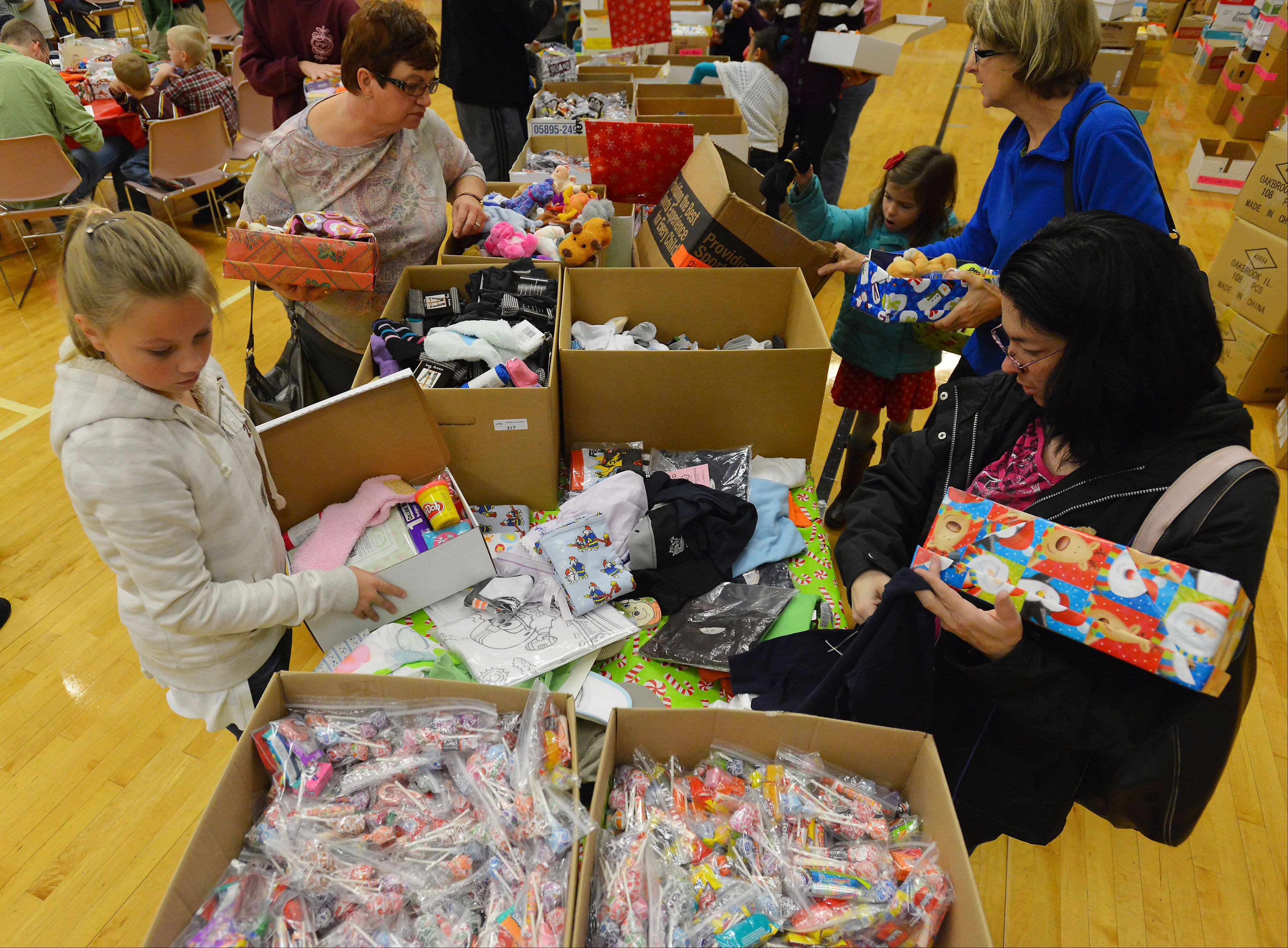 Volunteers pack shoe boxes with gifts, toys, hygiene items and school supplies Saturday at Immanuel Church in Gurnee as part of Operation Christmas Child. The church aimed to pack 4,000 gift boxes to be delivered to needy children in countries such as Congo, Cameroon and the Ukraine.