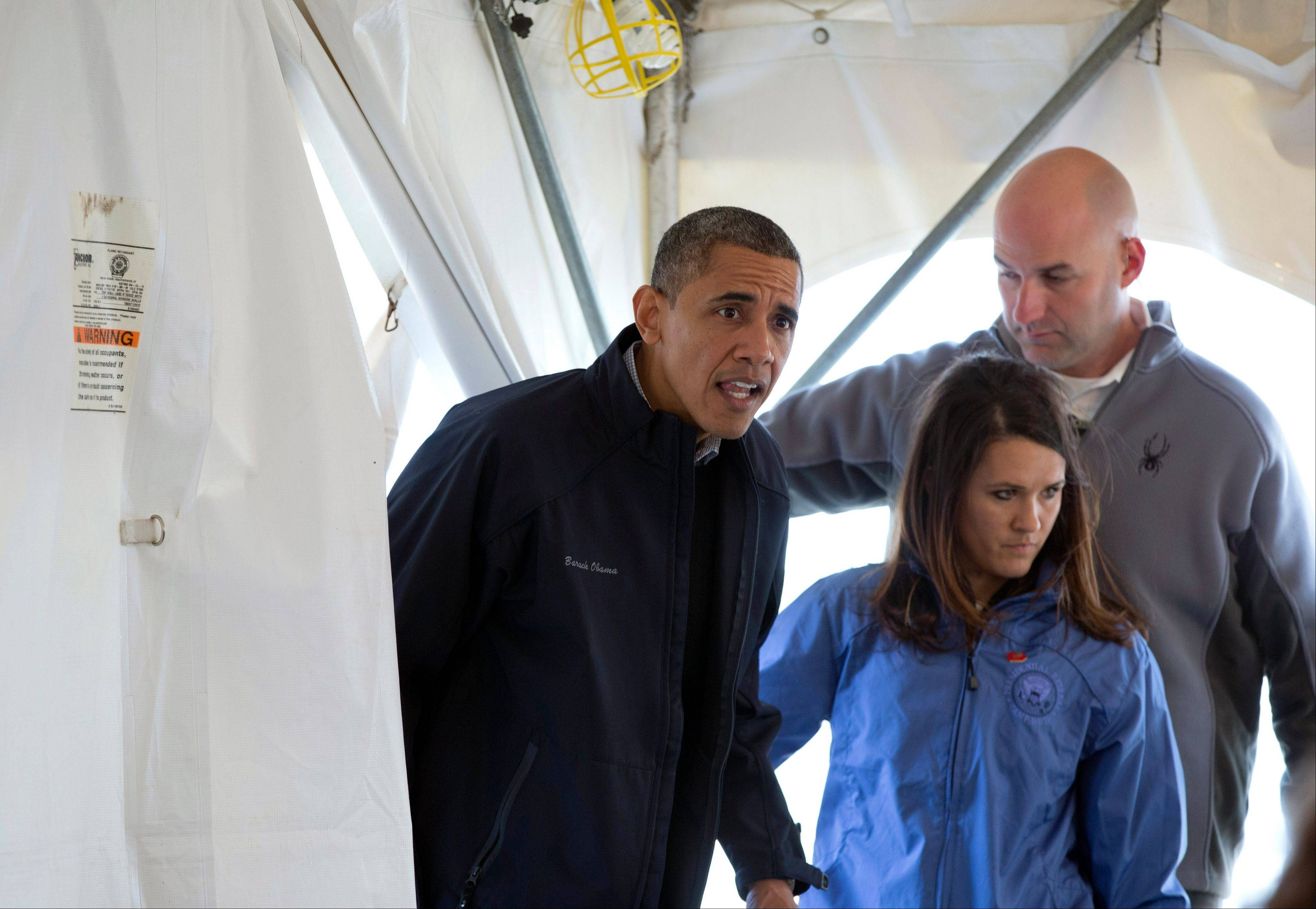 "President Barack Obama ducks into a tent to greet people at a FEMA recovery center on the grounds of New Dorp High School on the Staten Island borough of New York, Thursday. Obama vowed Thursday to stick with New Yorkers still struggling 17 days after Superstorm Sandy ""until the rebuilding is complete"" after getting an up-close look at devastated neighborhoods rendered unlivable."