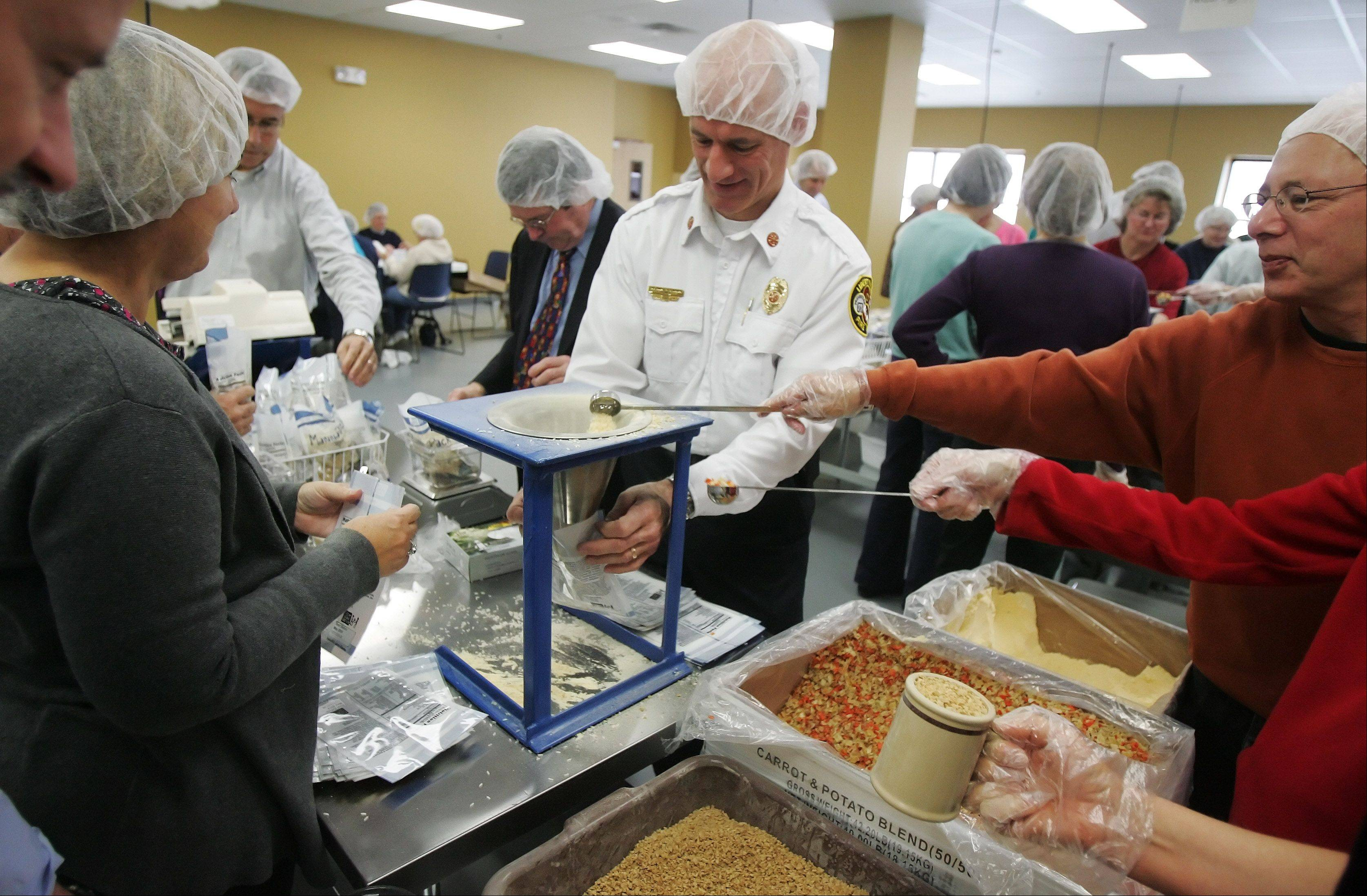 Libertyville Fire Chief Rich Careni, center, and Mayor Terry Wepler, left, join other volunteers during the inaugural meal-packing session Wednesday at Feed My Starving Children in Libertyville. The organization will now be able to prepare 70 million meals annually at the three Chicago area locations in Libertyville, Schaumburg and Aurora.