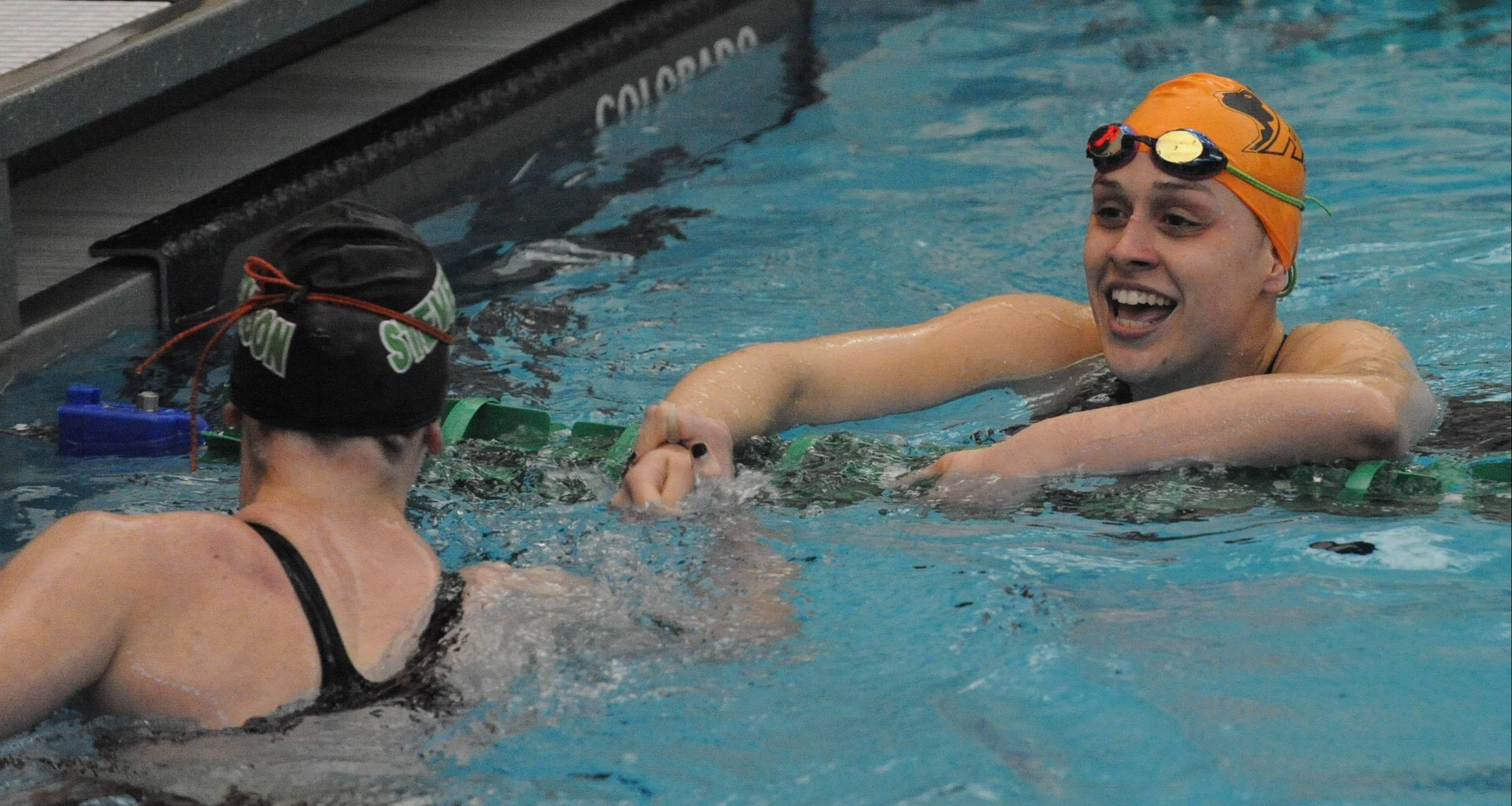Hersey's Amanda Petro, facing, and Stevenson's Madison Blaydes like their state-qualifying results in the 100-yard backstroke in last weekend's sectional meet.