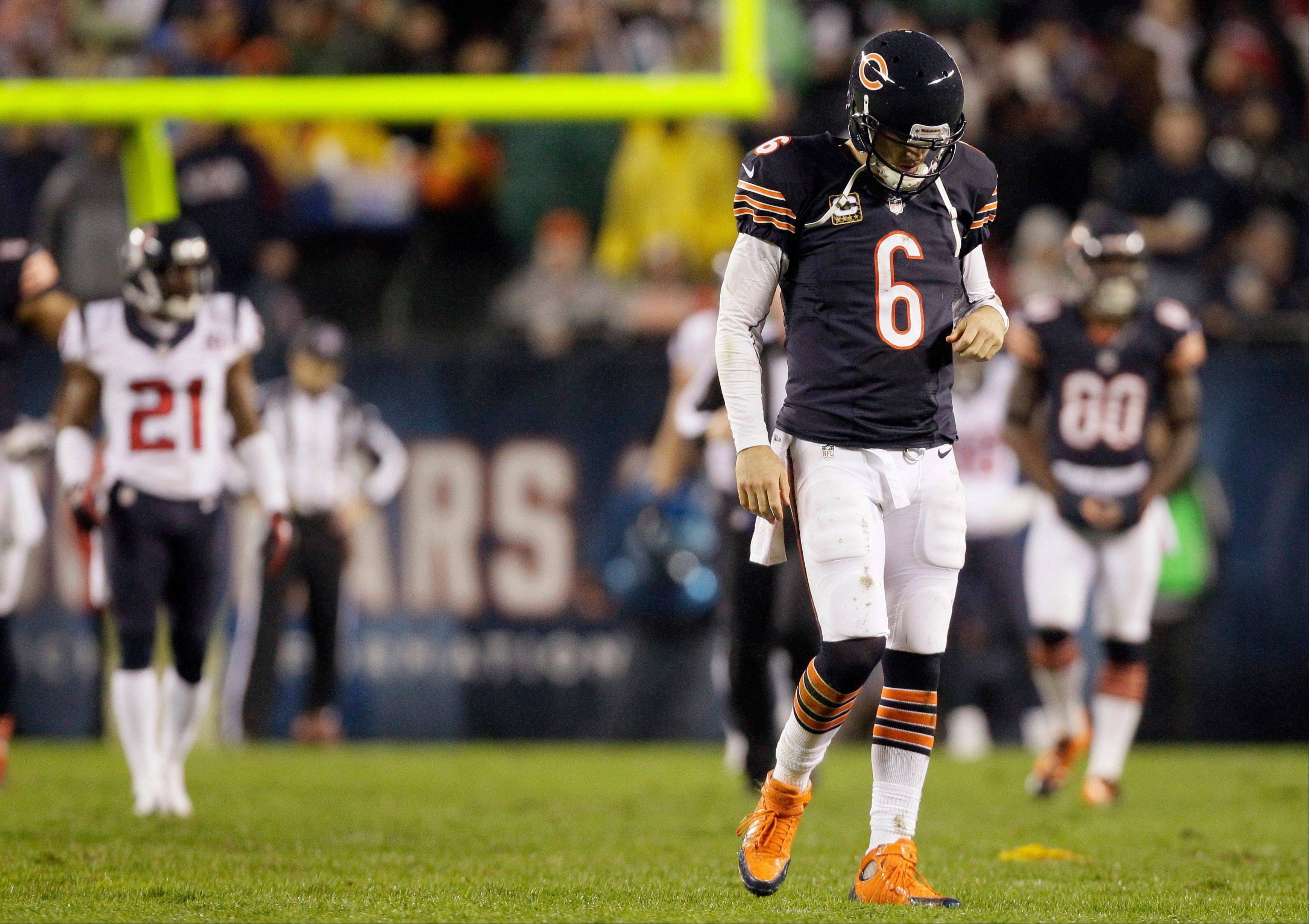 Bears quarterback Jay Cutler walks off the field Sunday after he threw an illegal forward pass and took a late hit by Houston Texans linebacker Tim Dobbins in the first half.