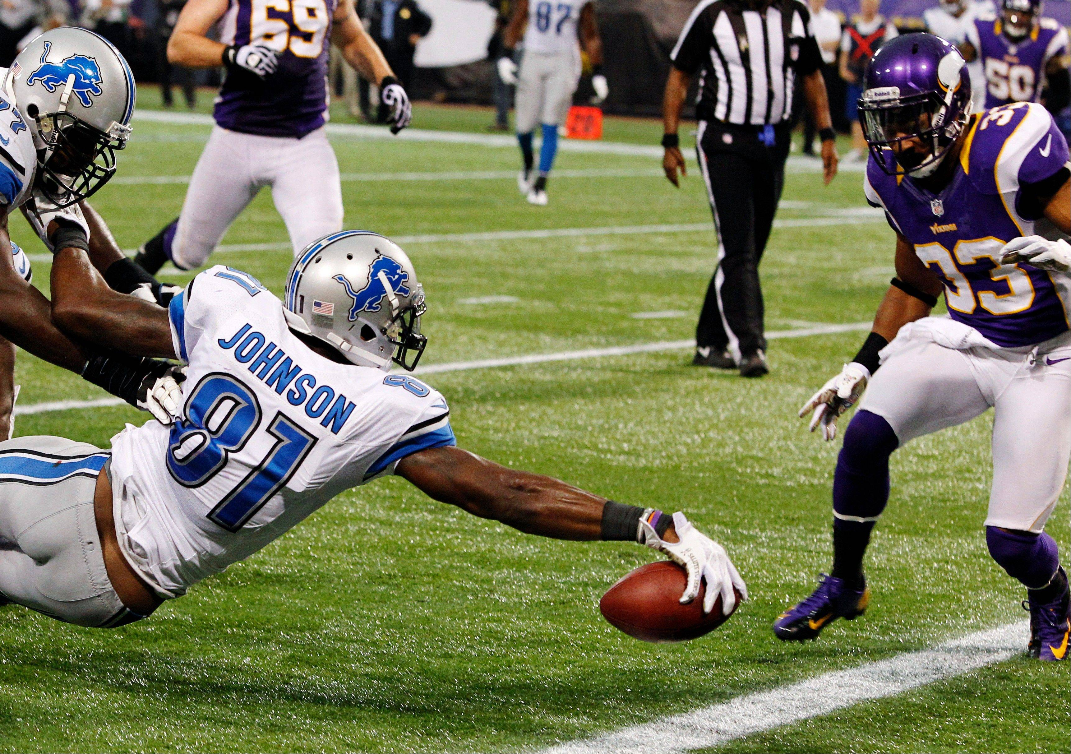 Detroit Lions wide receiver Calvin Johnson reaches for the end zone in front of Minnesota Vikings safety Jamarca Sanford while scoring on an 11-yard touchdown reception Sunday during the second half in Minneapolis.