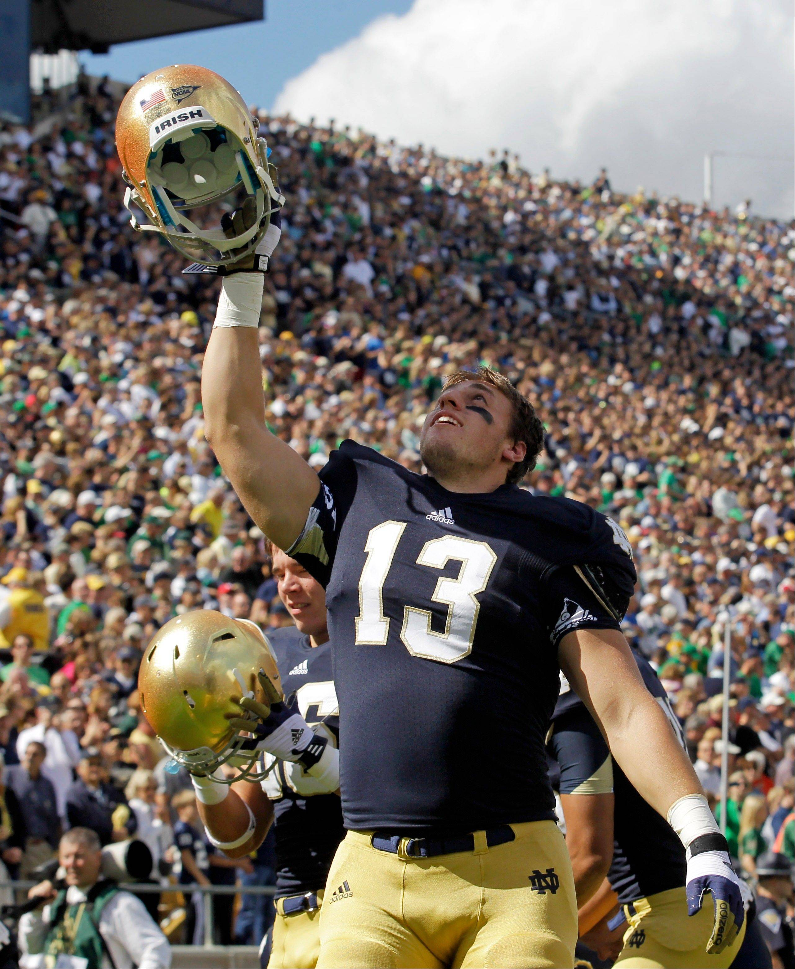 Notre Dame linebacker Danny Spond (13) cheers during the first half against Purdue in South Bend, Ind. The junior from Littleton, Colo., wasn't sure he'd play football again after he was struck by a debilitating migraine headache that left him barely able to move because the left side of his body was so numb. But after missing the first two games, Spond has bounced back and started eight games for the third-ranked Fighting Irish heading into Saturday's game against Wake Forest.