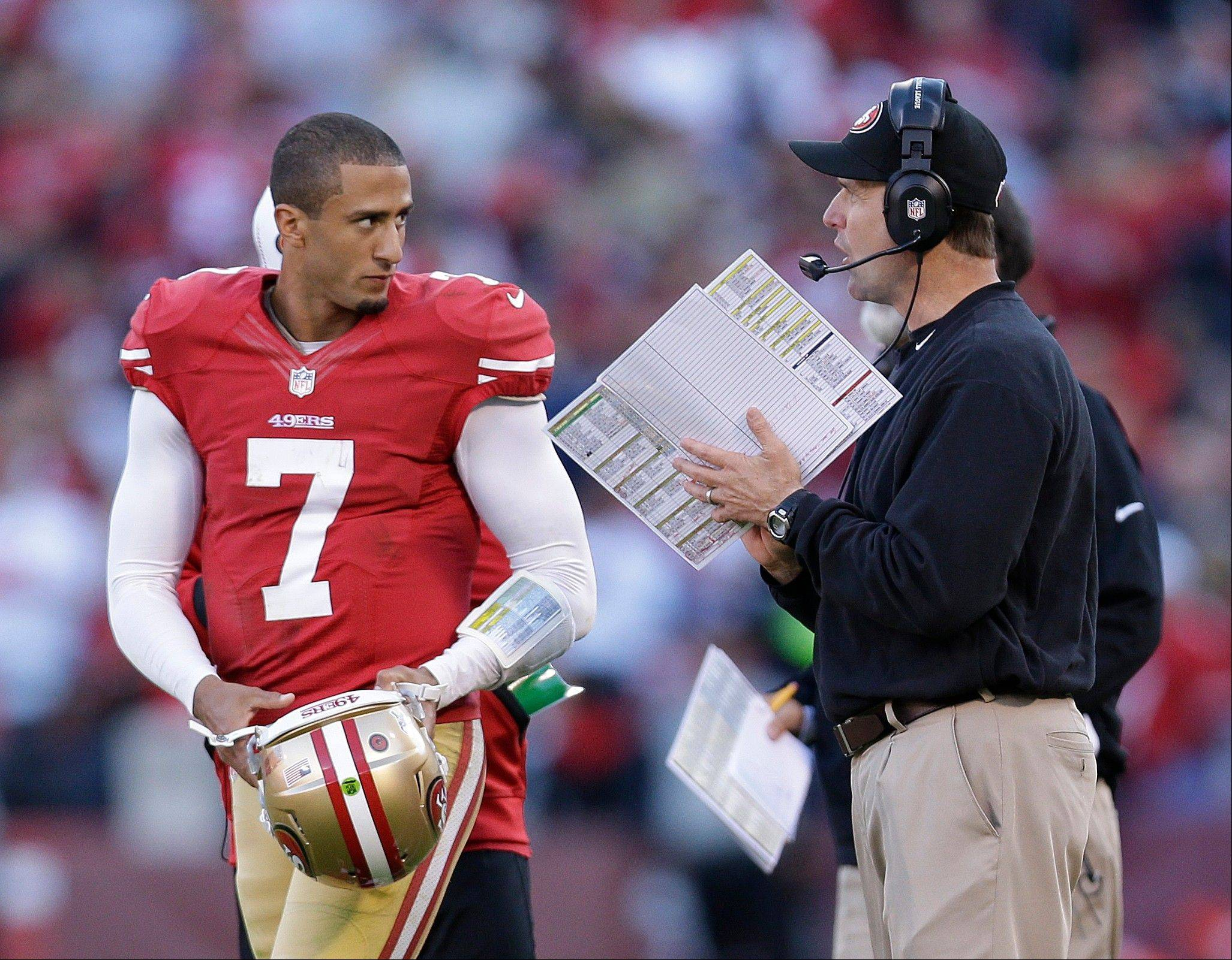 "San Francisco 49ers quarterback Colin Kaepernick talks with head coach Jim Harbaugh Sunday during the fourth quarter. Harbaugh has been sent to the hospital for a ""minor procedure"" after doctors discovered he had an irregular heartbeat."