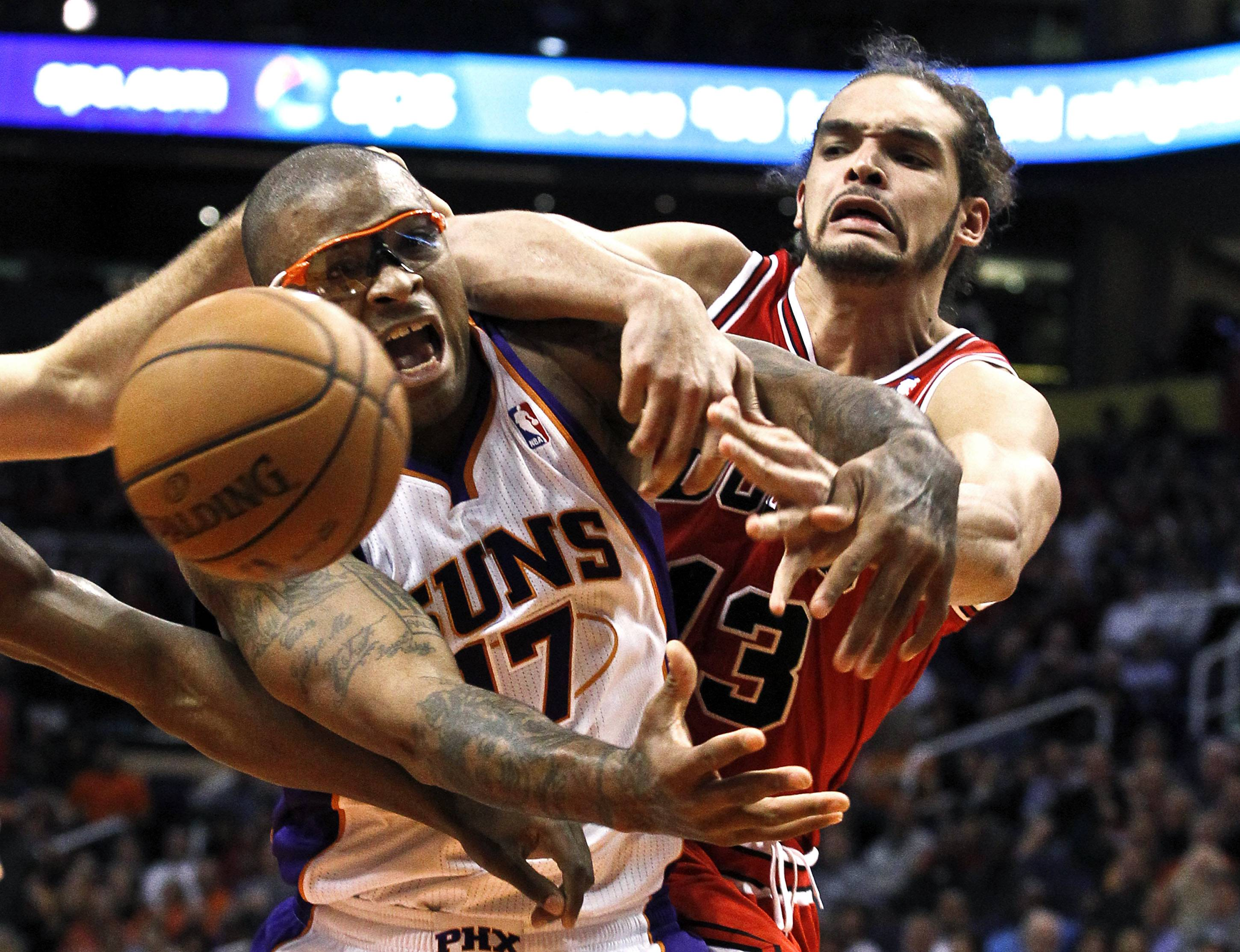 Phoenix Suns' P.J. Tucker (17) battles Chicago Bulls' Joakim Noah, right, for a loose ball during the second half of an NBA basketball game, Wednesday, Nov. 14, 2012, in Phoenix. The Bulls won 112-106.
