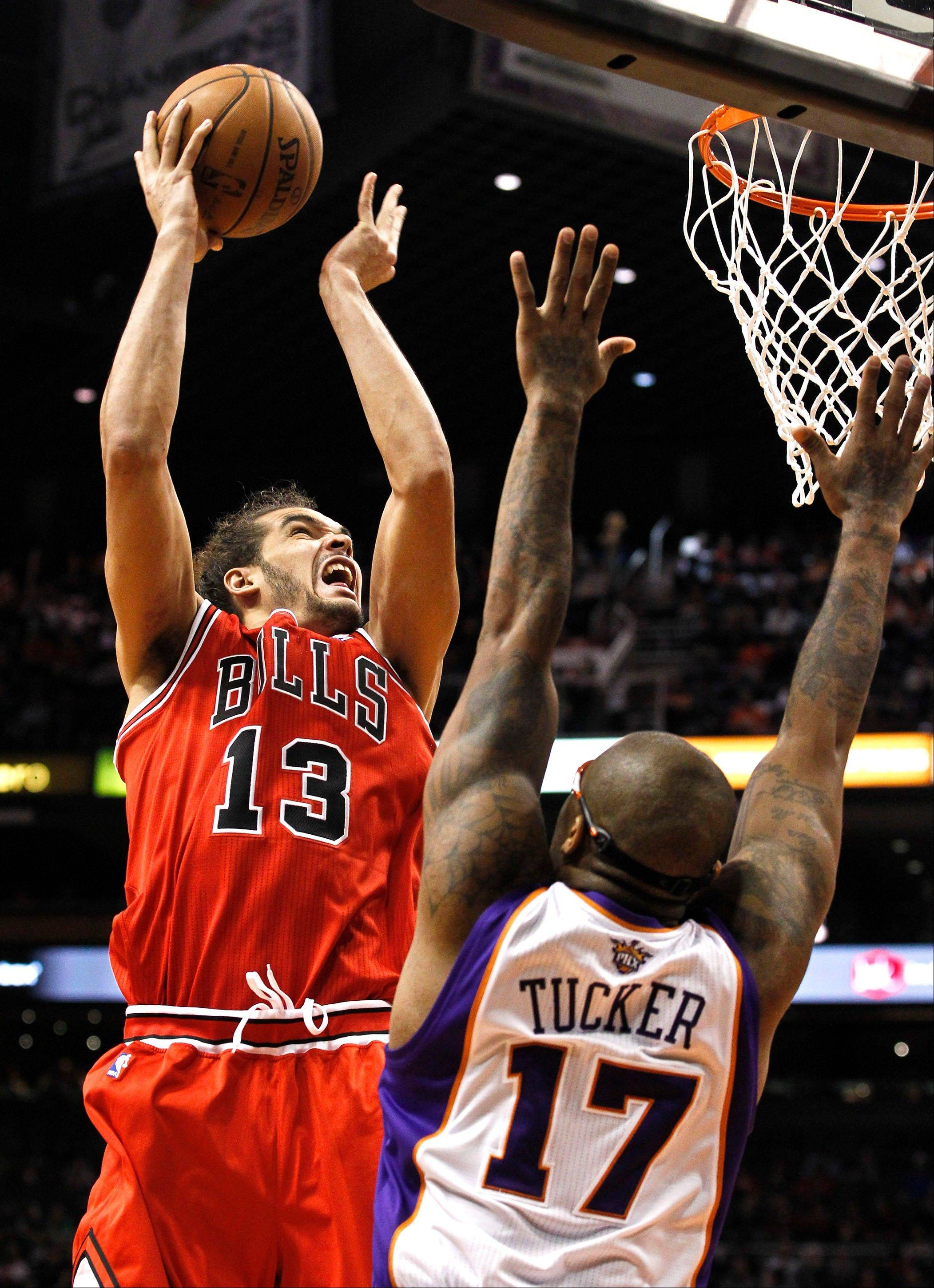 Chicago Bulls' Joakim Noah (13) shoots over Phoenix Suns' P.J. Tucker (17) during the first half of an NBA basketball game, Wednesday, Nov. 14, 2012, in Phoenix.