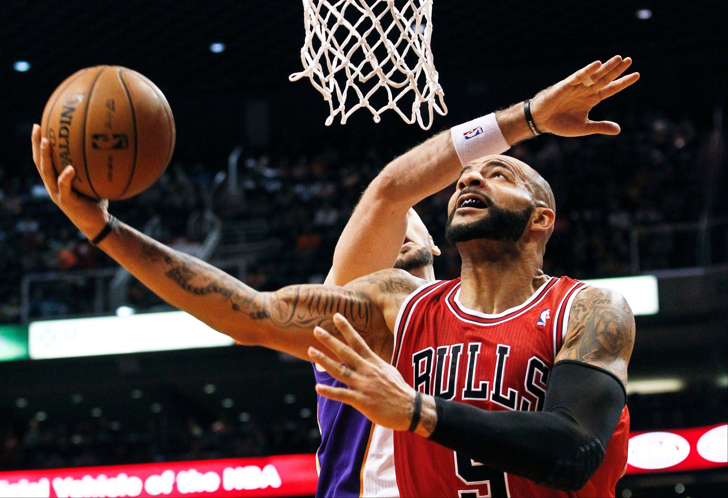 Bulls forward Carlos Boozer, front, shoots past the Phoenix Suns' Marcin Gortat Wednesday during the first half in Phoenix.