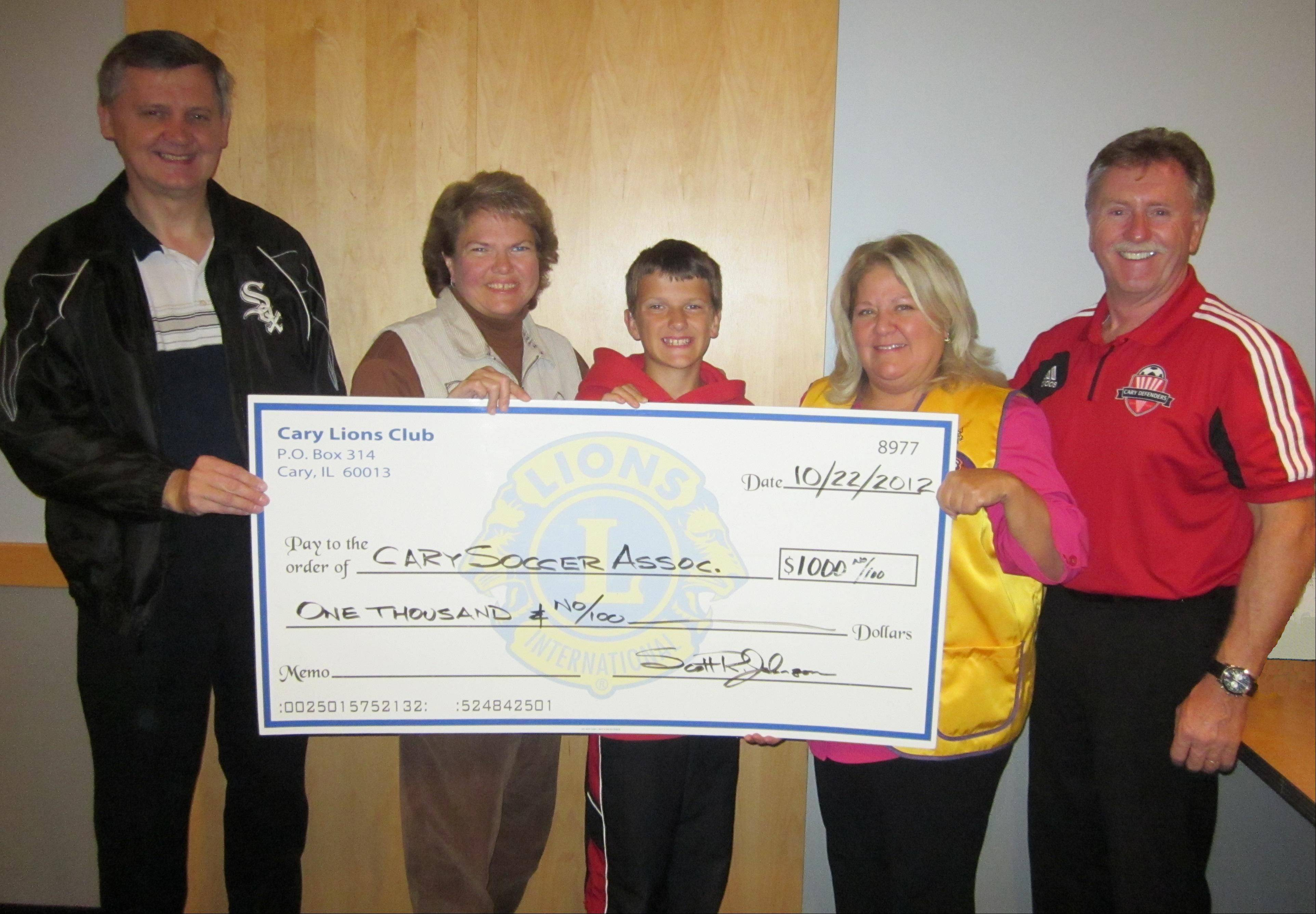 Mark and Ellen Wisniewski, left, join their son Andrew Wisniewski, a hearing-impaired participant in the soccer program, in thanking Cary Lions president Holly Kelps and Hughie O'Malley, president of the Cary Soccer Association, for the donation.