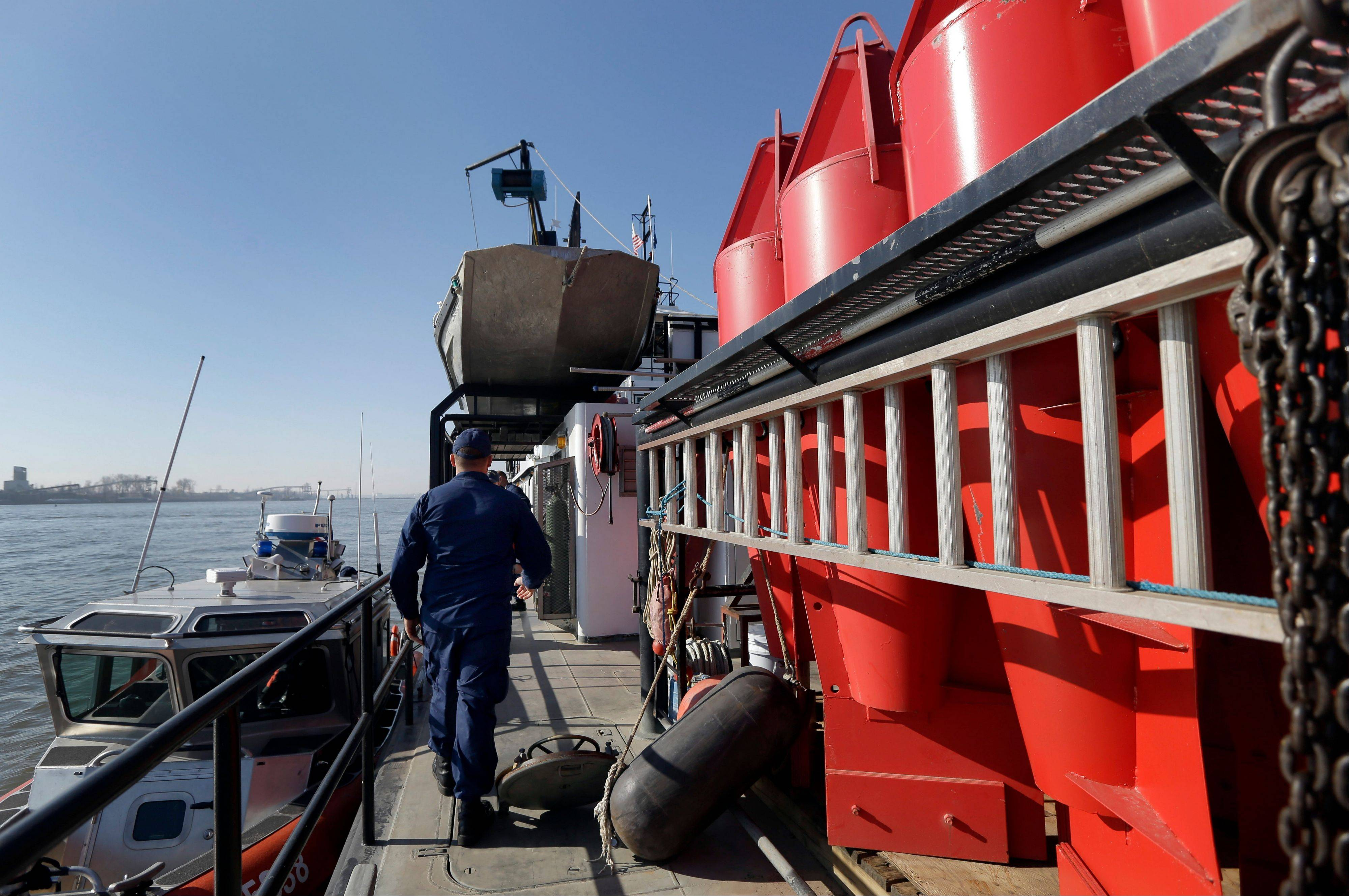 A member of the U.S. Coast Guard walks Friday on the deck of a barge used to place navigational buoys, seen at right, along the Mississippi River to aid vessels as they travel up and down the waterway.