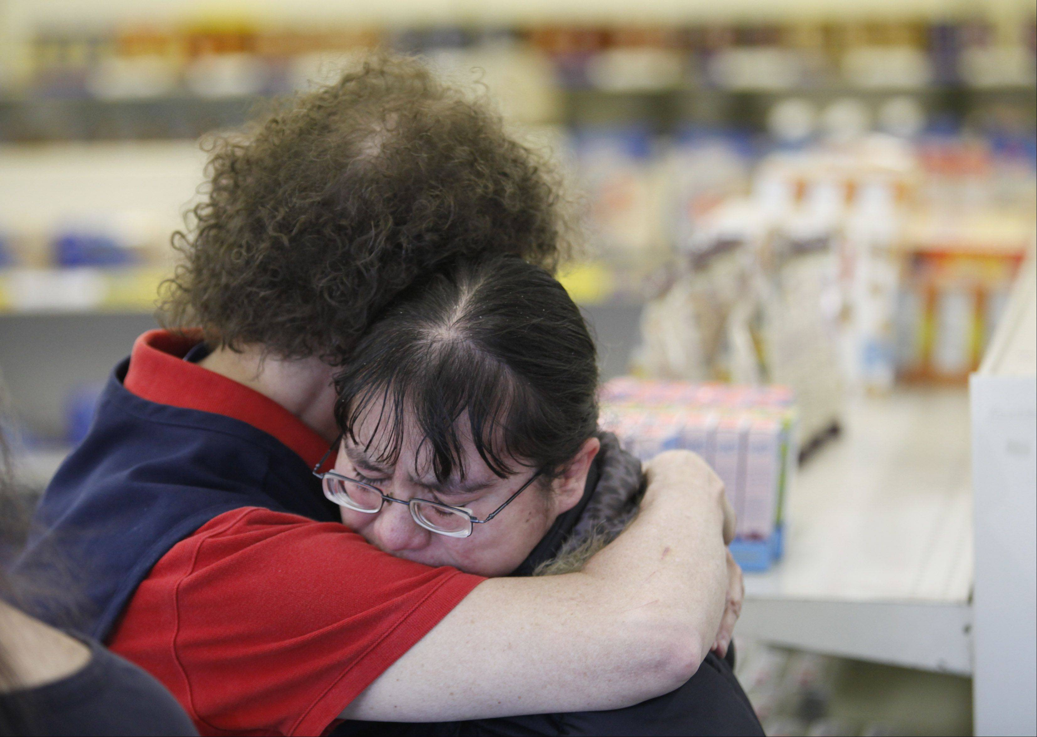 Wonder Hostess Thrift Shop employee Kathy Lipprandt, left, hugs fellow employee A.J. Galvan Friday after it was announced the Hostess company was calling it quits.