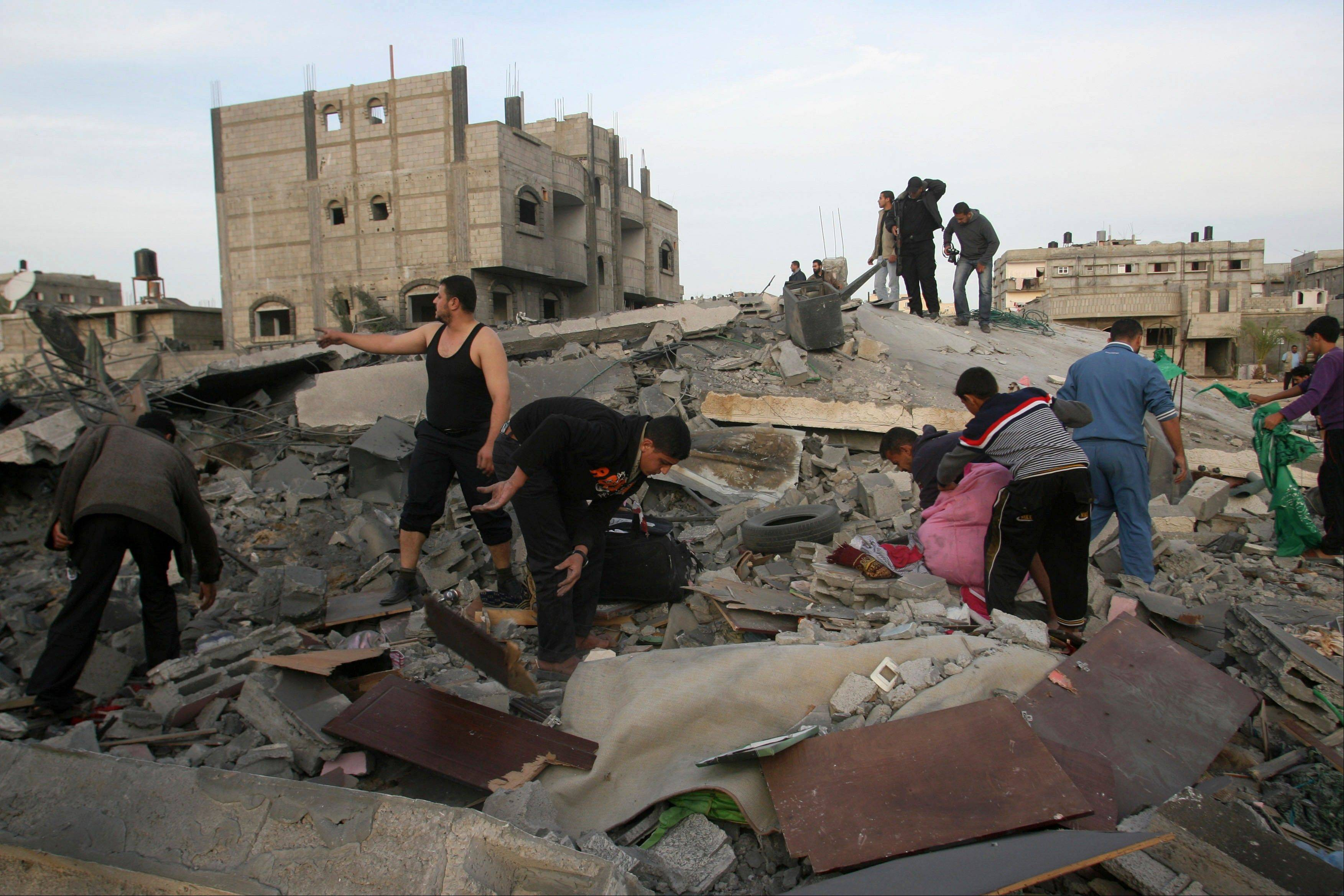 Palestinians inspect the rubble of the destroyed house of Hamas militant Mohammad Abu Shmala, following an Israeli air strike in Rafah, southern Gaza Strip, on Friday.