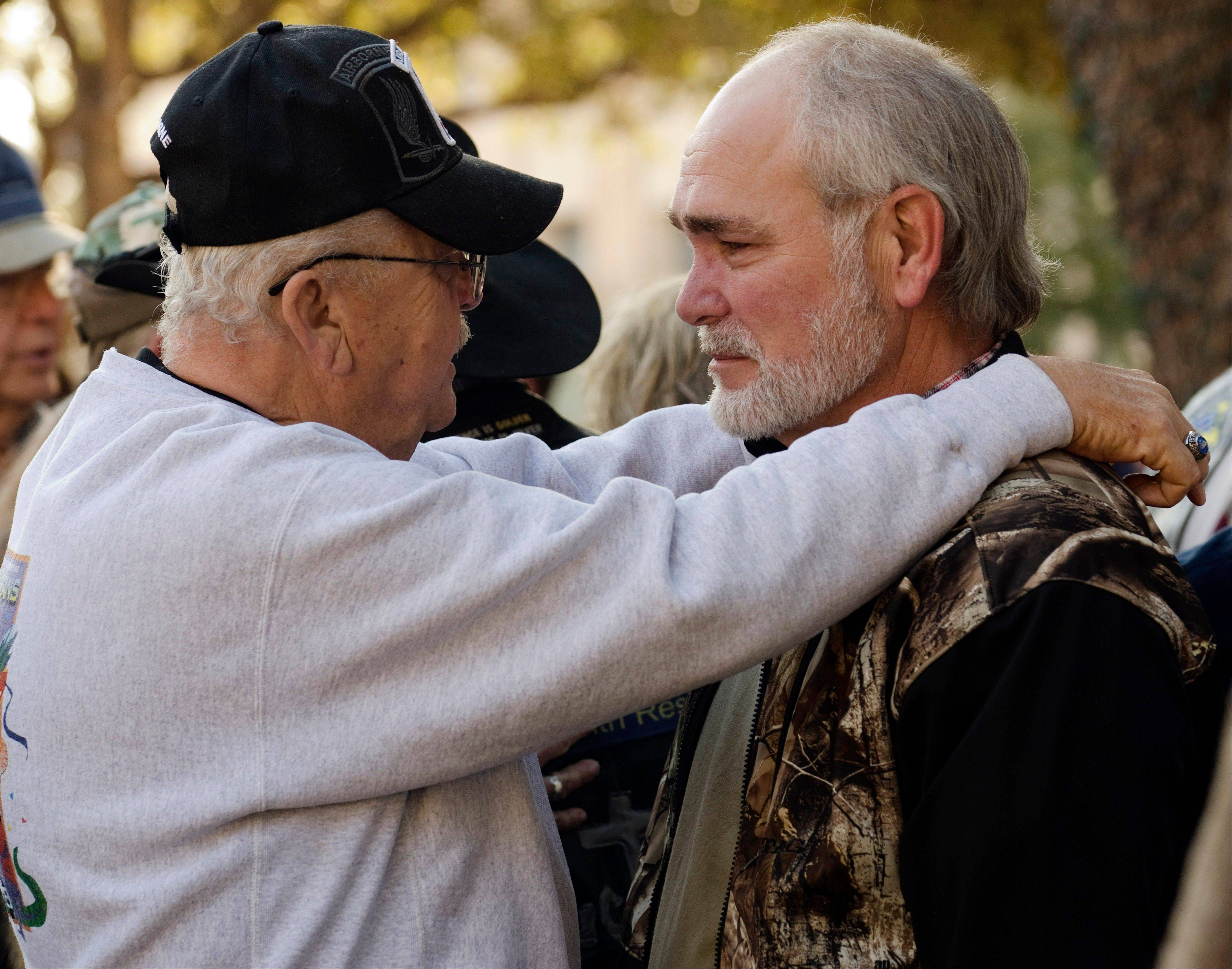 Johnie Lee Qualls, left, comforts and talks Friday with Terry Johnson, in Midland, Texas, before a community prayer service to pray for all those involved in an accident Thursday, where four veterans were killed.