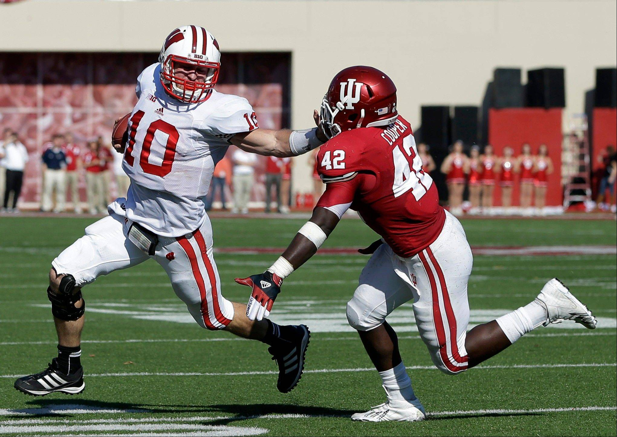 Wisconsin quarterback Curt Phillips (10) is chased by Indiana's David Cooper during the first half of an NCAA college football game, Saturday, Nov. 10, 2012, in Bloomington, Ind. (AP Photo/Darron Cummings)