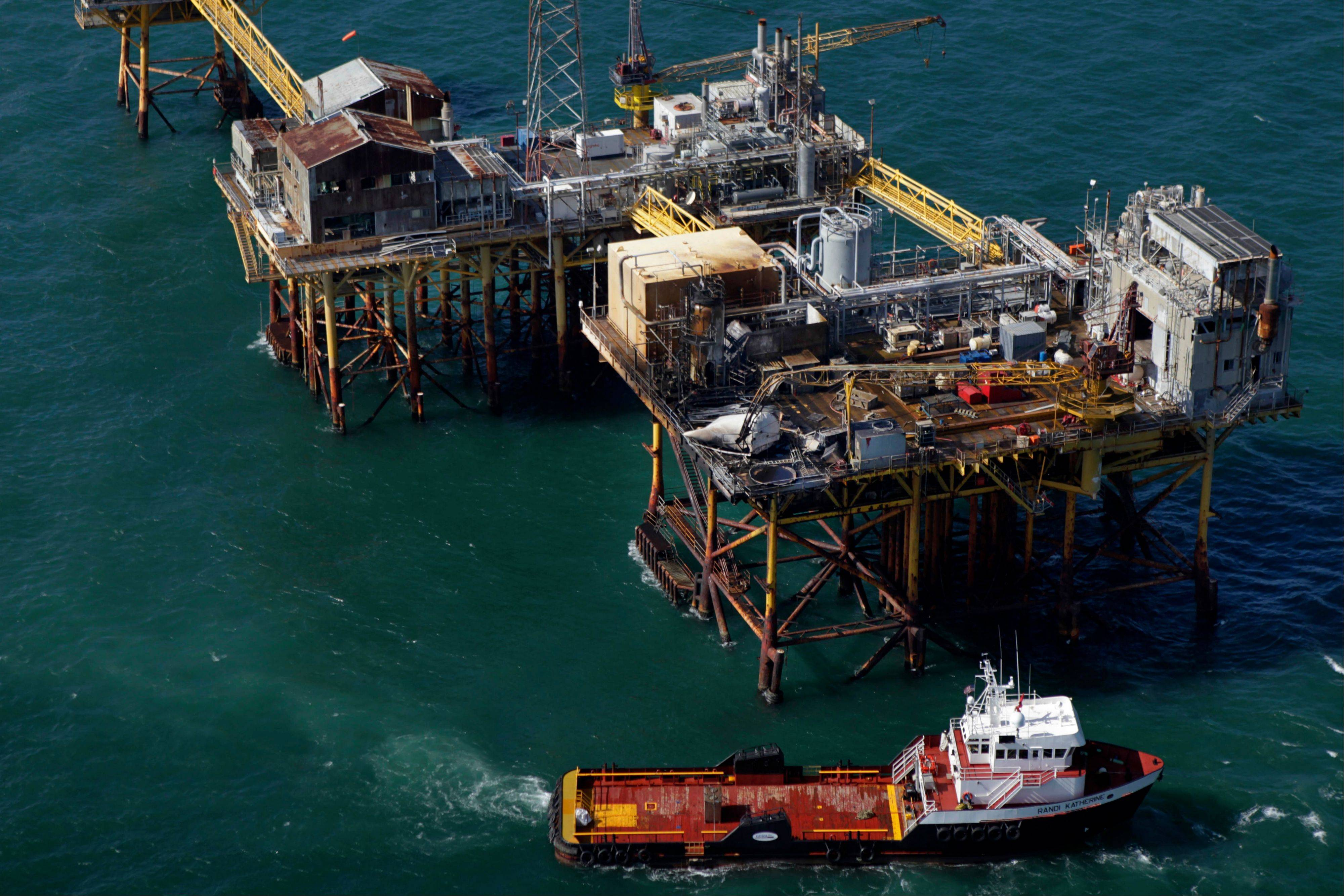 In this aerial photograph, a supply vessel moves Friday near an oil rig damaged by an explosion and fire.