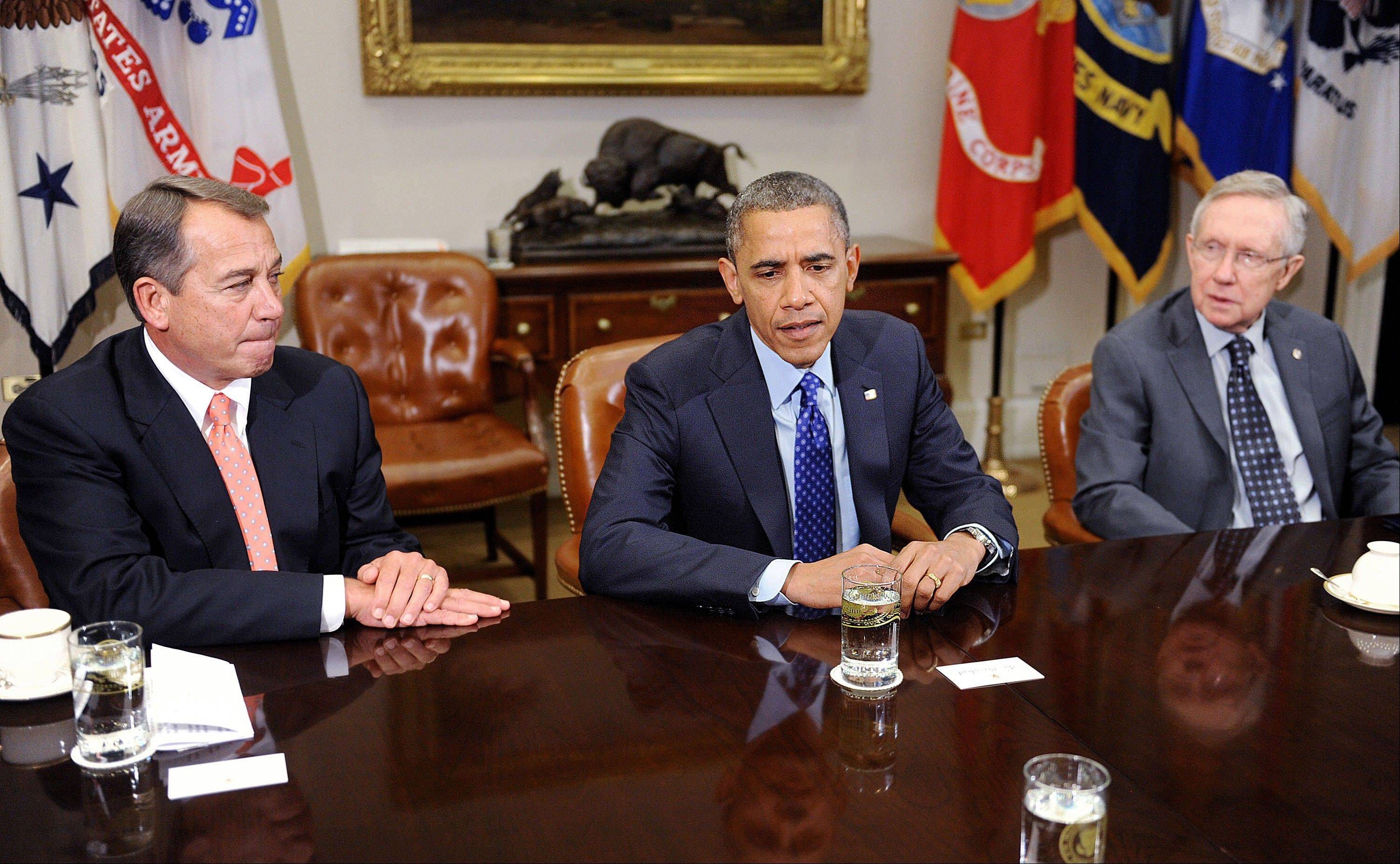 President Barack Obama, center, speaks while House Speaker John Boehner, a Republican from Ohio, left, and Harry Reid, a Democratic Senator from Nevada, listen Friday during a meeting in the Roosevelt Room of the White House.