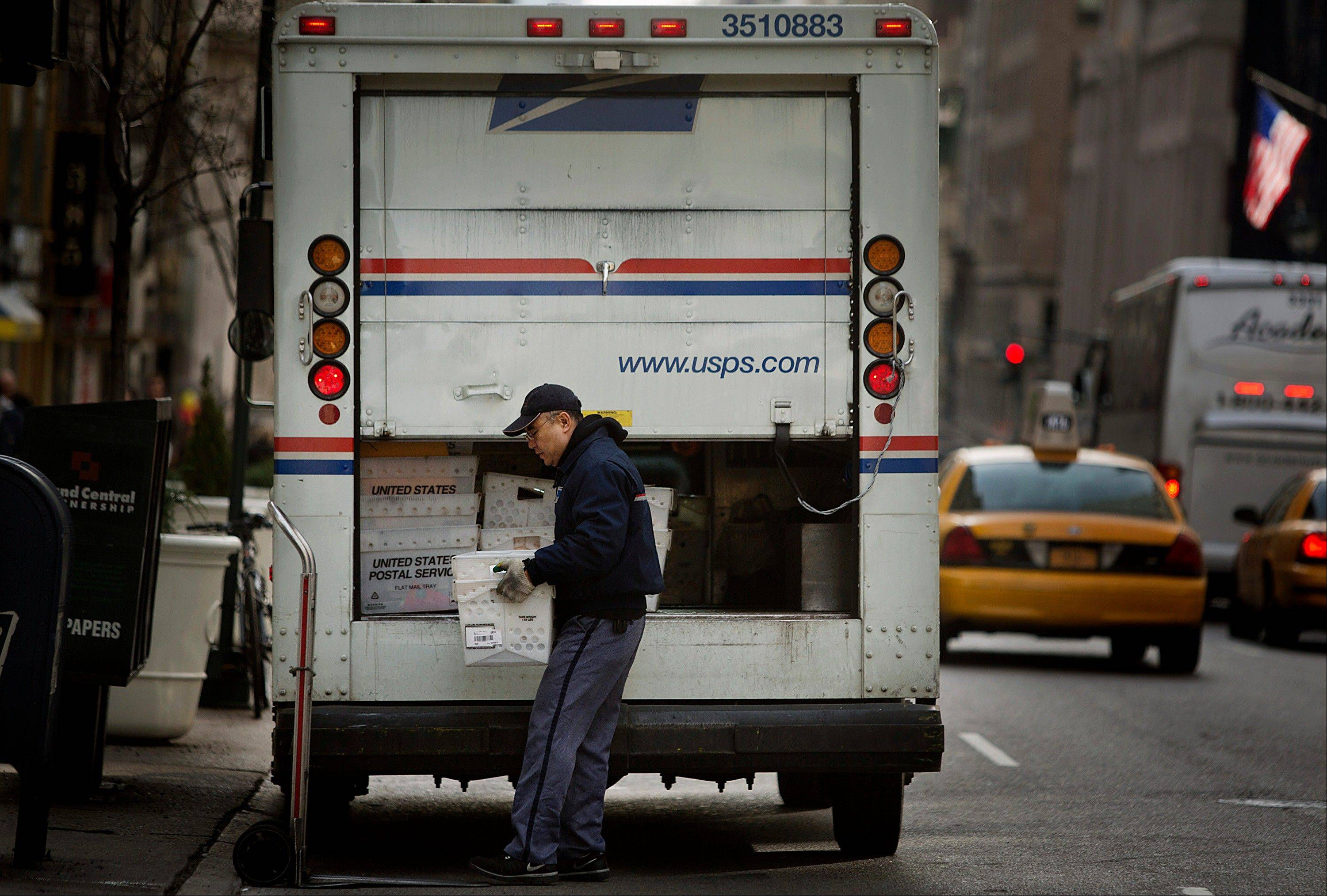 A U.S. Postal Service employee takes mail out of a truck Thursday for delivery in New York on Thursday.