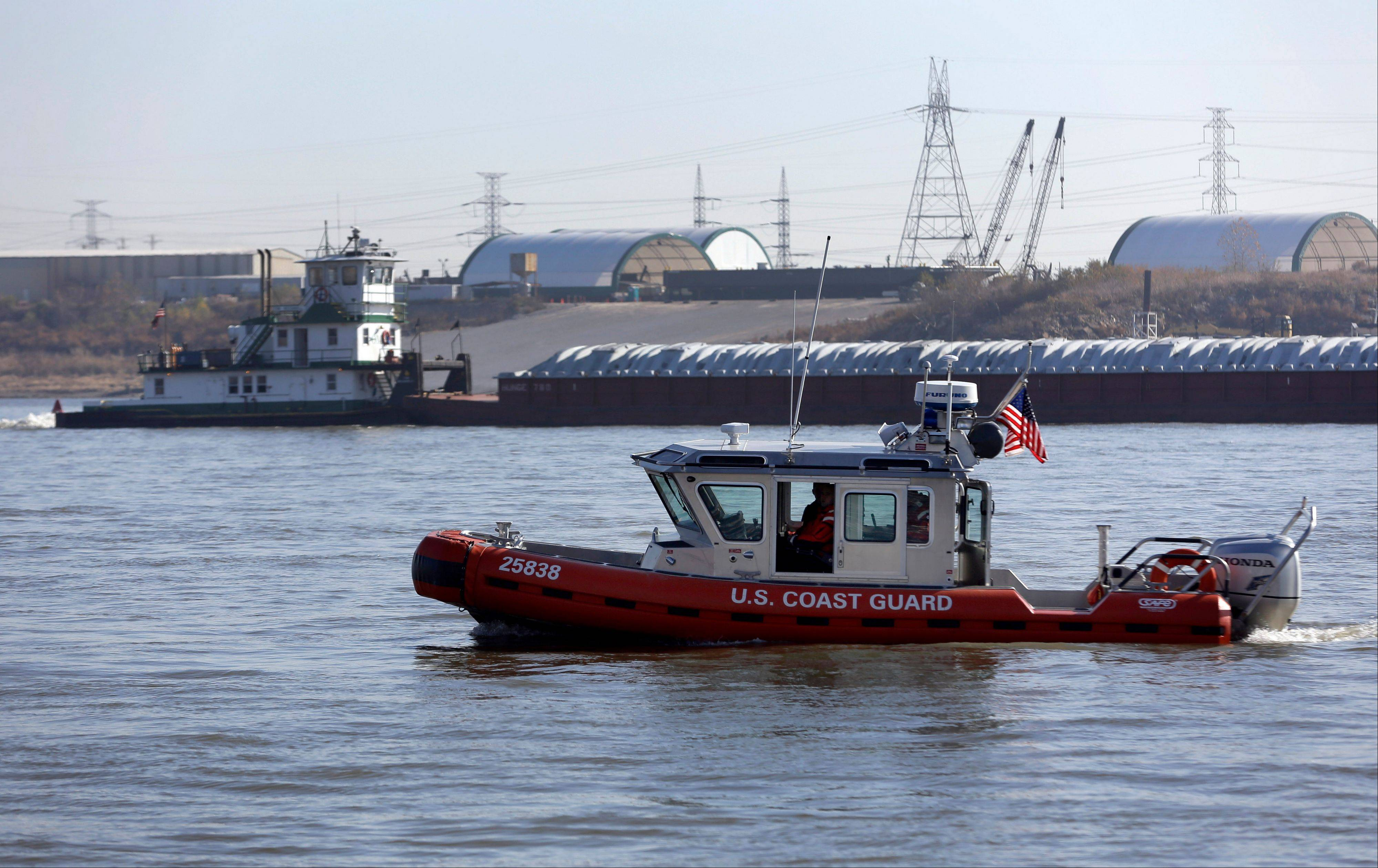 Associated Press A Coast Guard boat patrols in the foreground as a barge makes its way down the Mississippi River Friday in St. Louis.