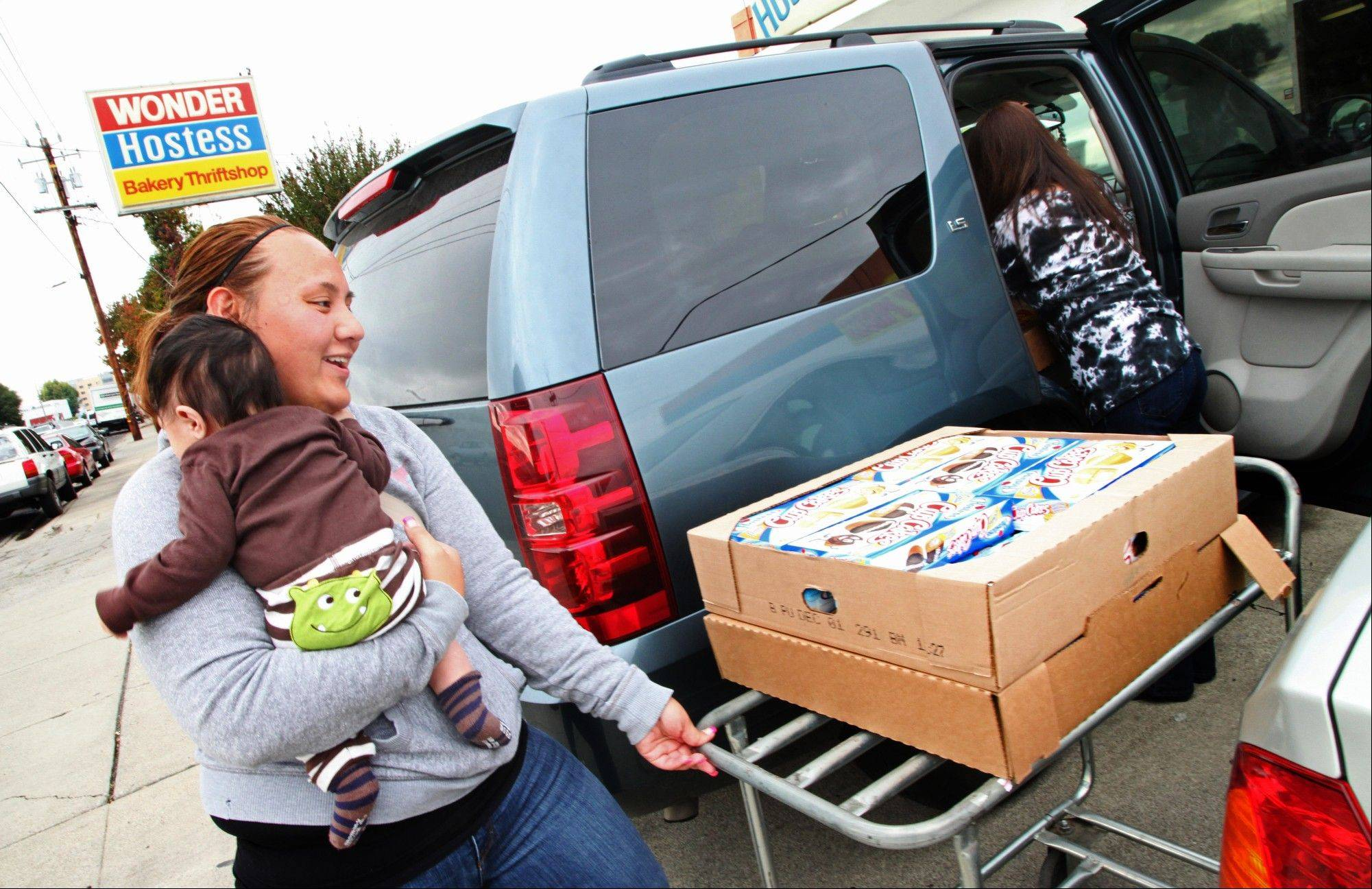 Vanessa Fifita, from San Leandro, left, puts boxes of Hostess products into her car Friday with the help of a worker outside the Hostess Bakery Thriftshop in San Leandro, Calif. on Friday, Nov. 16, 2012. With the announcement that the Hostess bakery is join out of business, Fifita's friends and relatives urged her to go to the thrift shop to pick up as many of the Hostess bakery products as possible.
