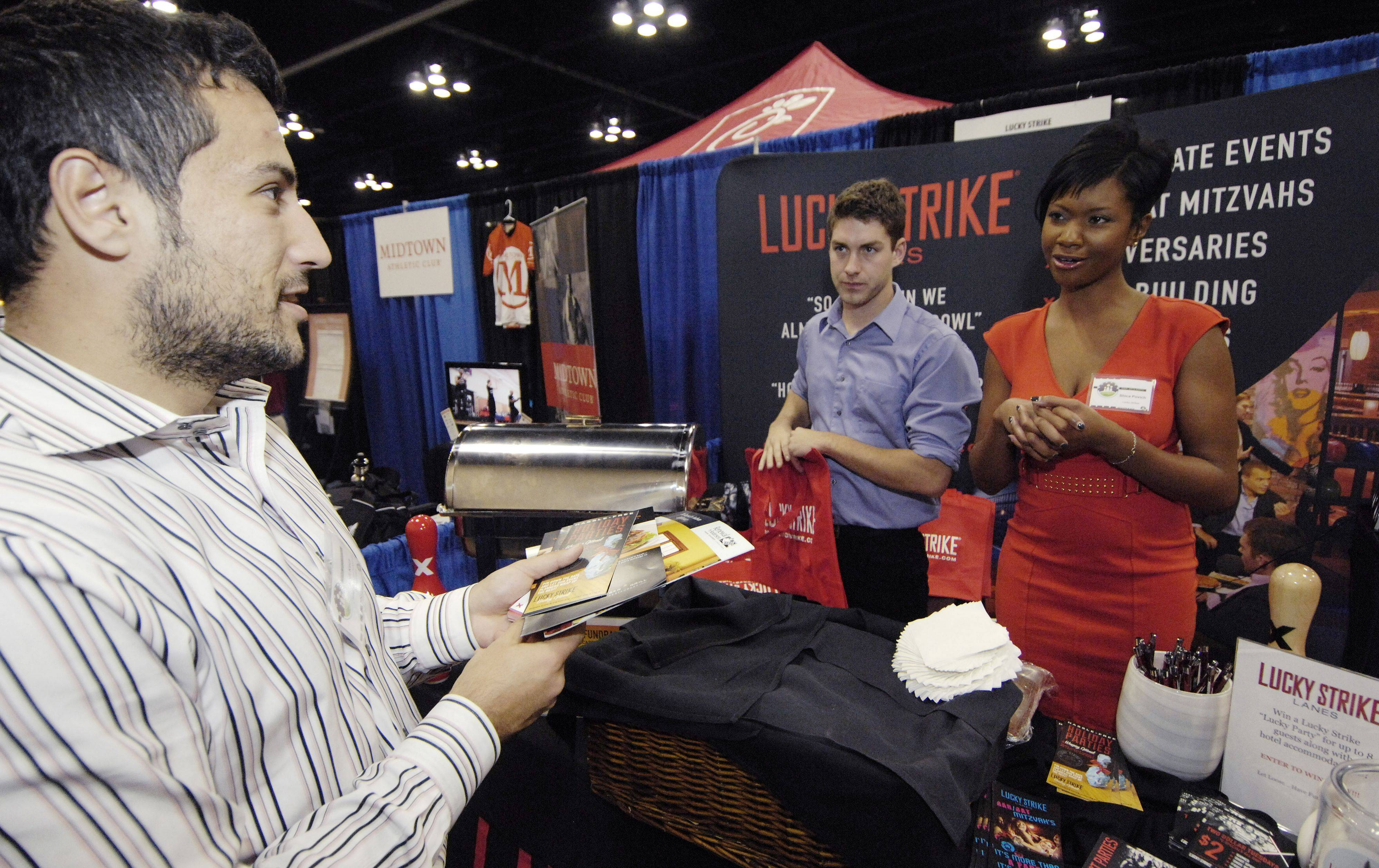 Andi Keca of the Keller Graduate School of Management speaks with Jason Gerren and Shica Povich of Lucky Strike Lanes during the Schaumburg Business Association expo Thursday. Story on Page 4