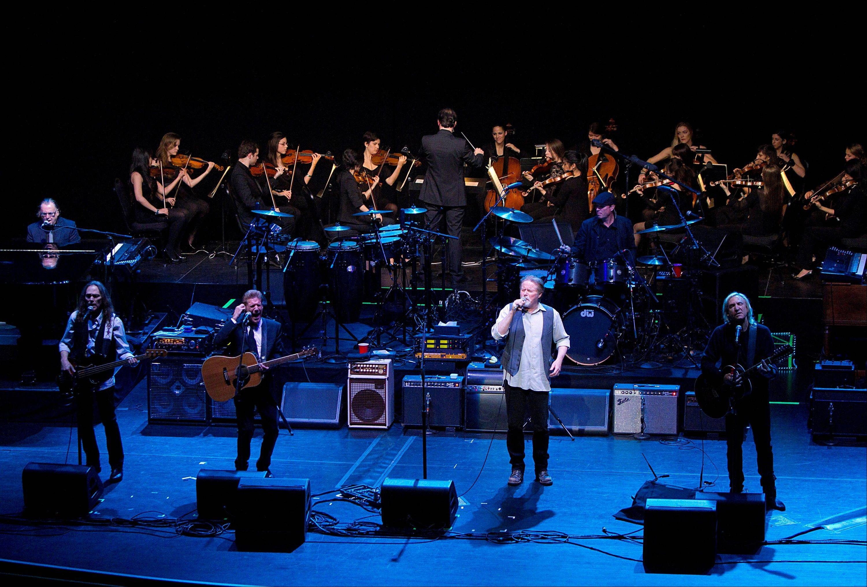 The NYU Steinhardt orchestral string ensemble performs with members of the Eagles, foreground from left, Timothy B. Schmit, Glenn Frey, Don Henley and Joe Walsh at the Inaugural Vision Award Gala Thursday in New York.