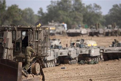 Israeli soldiers work on their a tanks in a staging ground near the border with Gaza Strip, southern Israel, Friday.