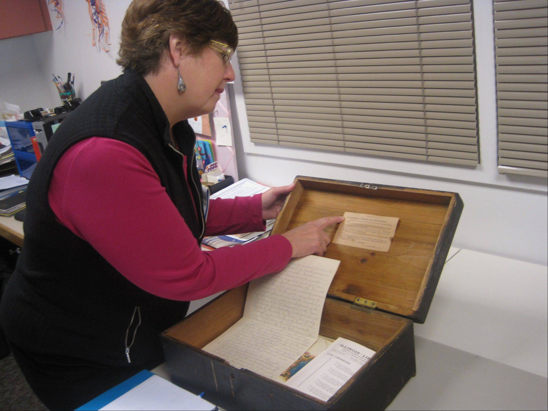 "Sharon Roundy, a volunteer with the Tree Climbers ancestry group at the Ella Johnson Memorial Public Library in Hampshire, points to some of the essays and letters people used to read at the turn of the 20th century during the so-called ""Wednesday Club."" The library is working on digital archive collections of such materials."