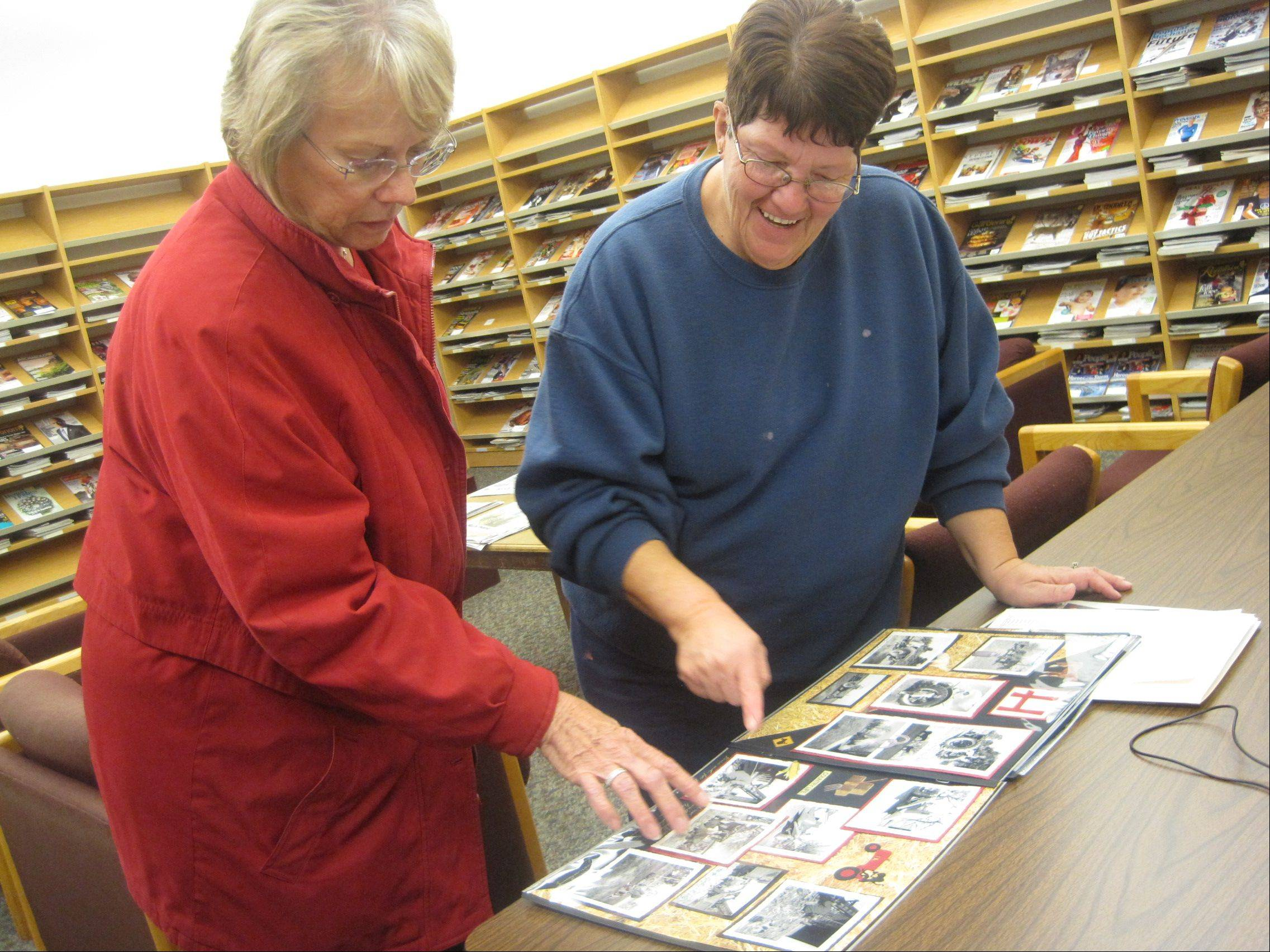 "Valerie Ruth of Hampshire and Carolyn Gathman of Plato Township look through Gathman's album of black-and-white photos of her family's farm in the 1940s and 1950s. Both participated in ""Digital Donation Day"" on Saturday at Ella Johnson Memorial Public Library District."