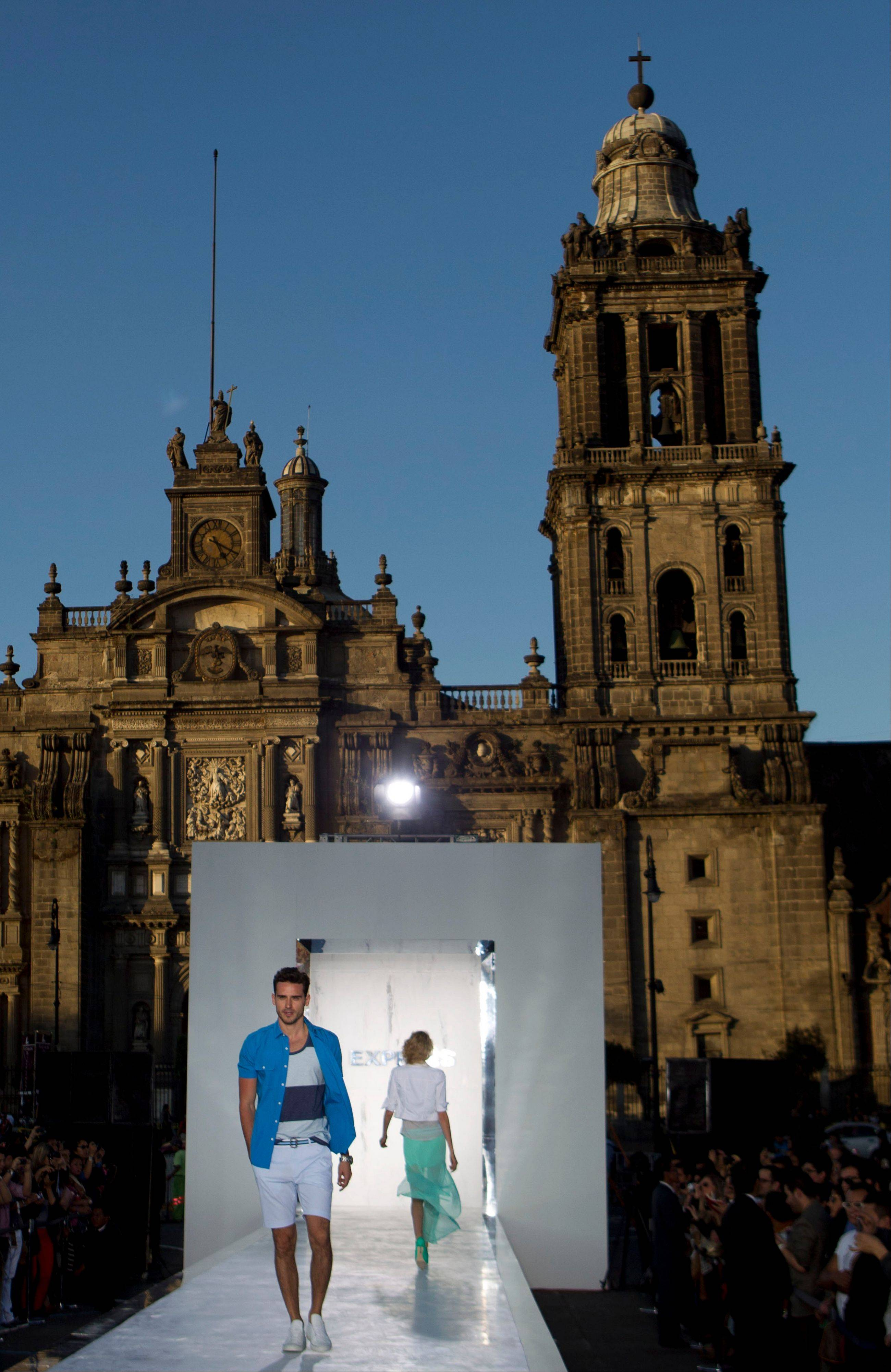"Associated Press Backdropped by the Metropolitan Cathedral, models wear creations from Express during their ""Rock The Sidewalk,"" event on the main plaza in Mexico City."
