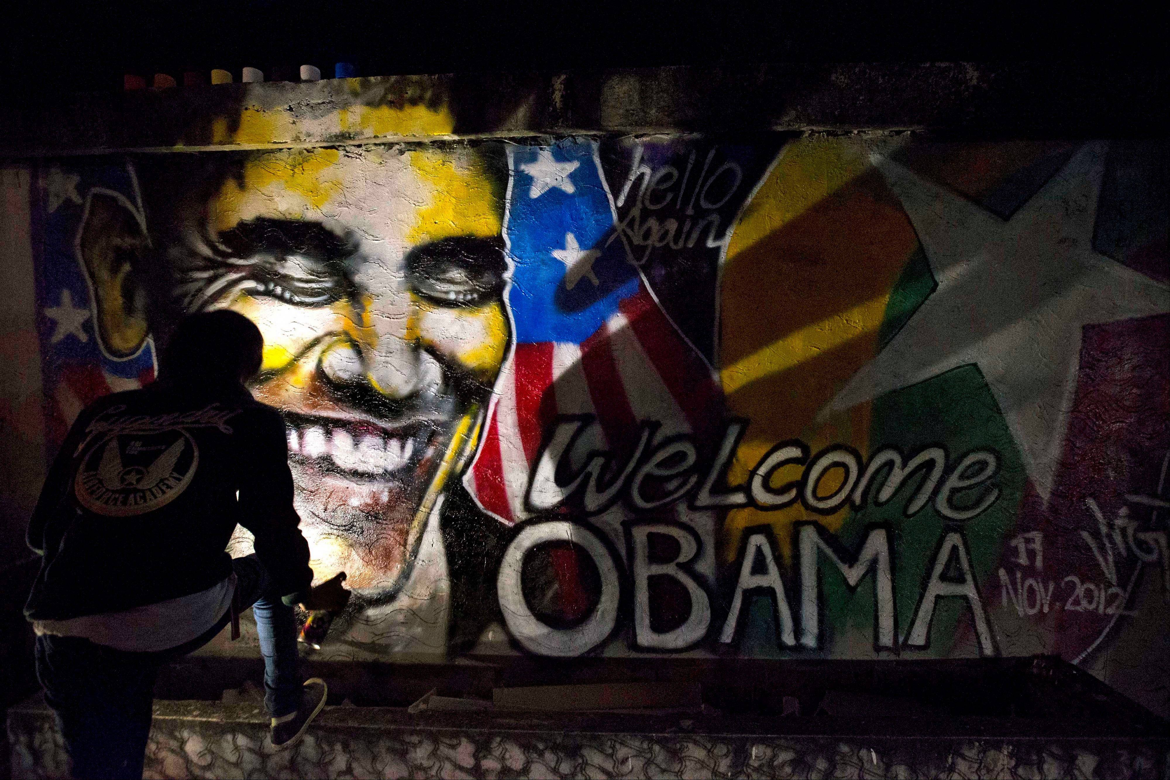 ArtistArker Kyaw paints a graffiti welcoming U.S. President Barack Obama in Yangon, Myanmar, at dawn on Saturday.