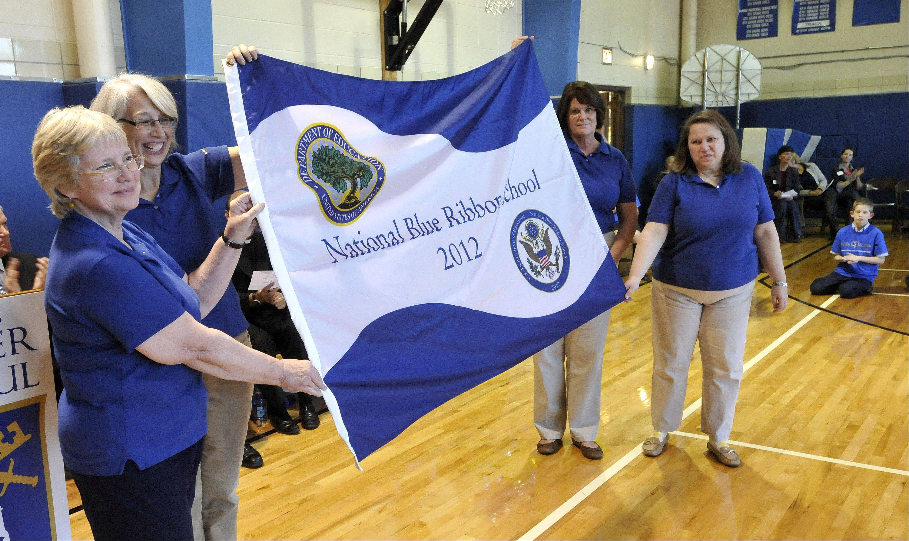 Veteran teachers Maura Gleason, Sue Gensler, Mary Skroch and Penny Schur display the Blue Ribbon flag that will fly over Ss. Peter and Paul for the rest of the school year.