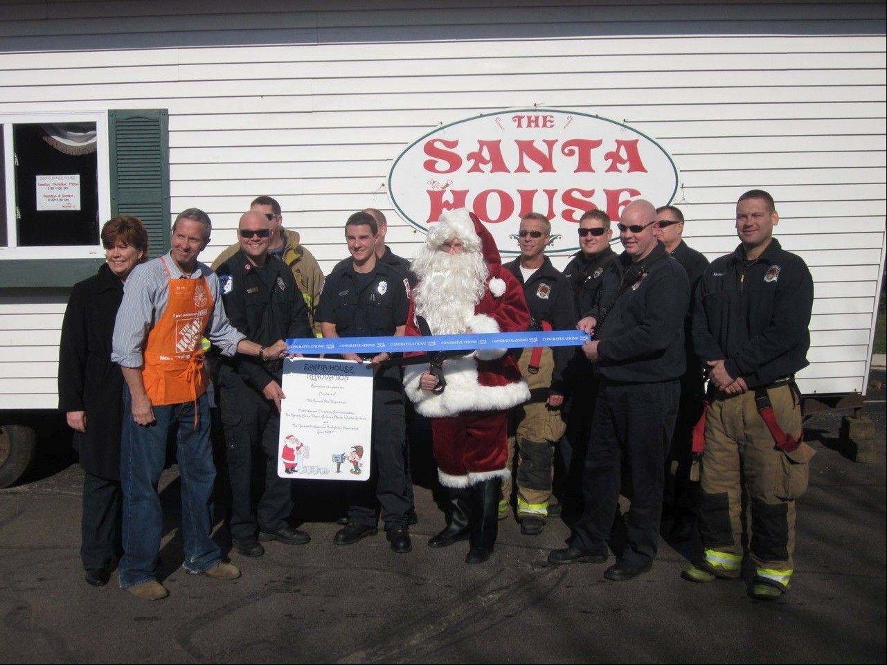 Representatives of the Geneva Fire Department, the Geneva Home Depot store and the Geneva Chamber of Commerce celebrate the refurbishment of the Santa House.