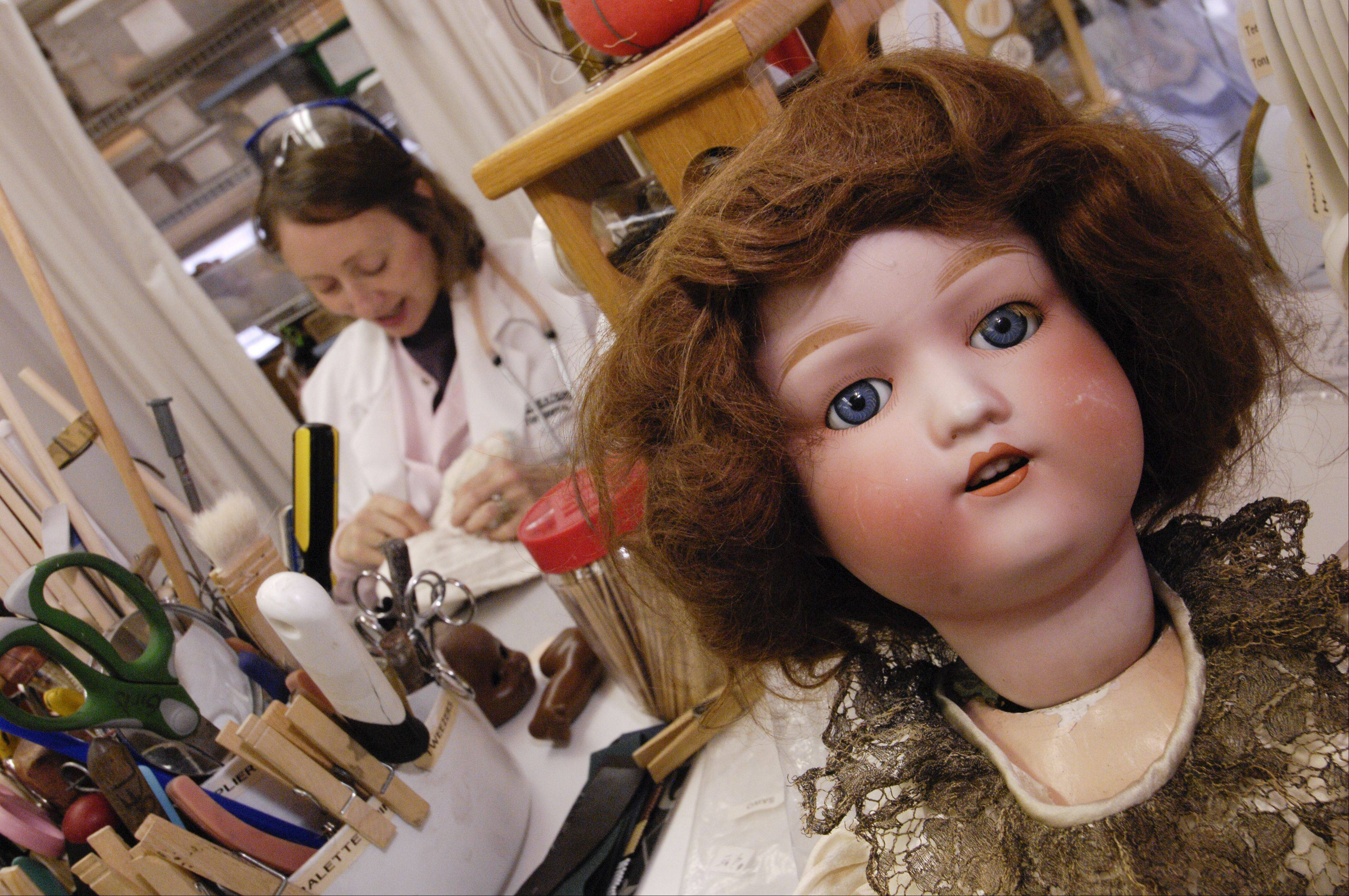 Angel Whitt sews the head back on 32-year-old bunny while an antique doll waits to be seen.