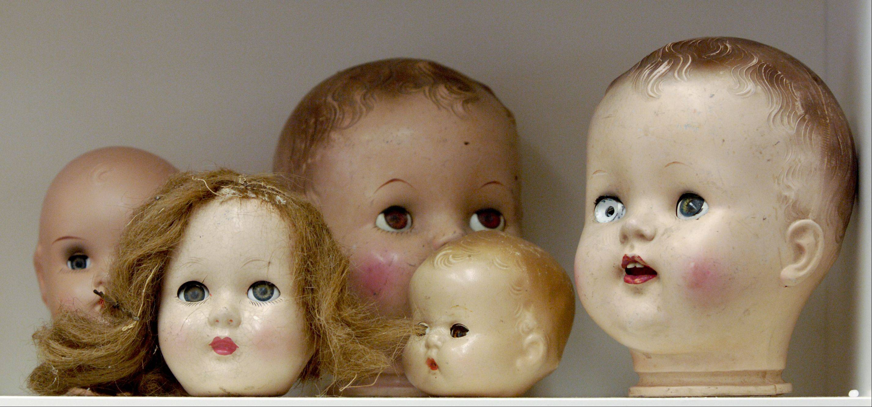 Antique doll heads sit on a shelf at the Angelic Creations Doll Hospital.