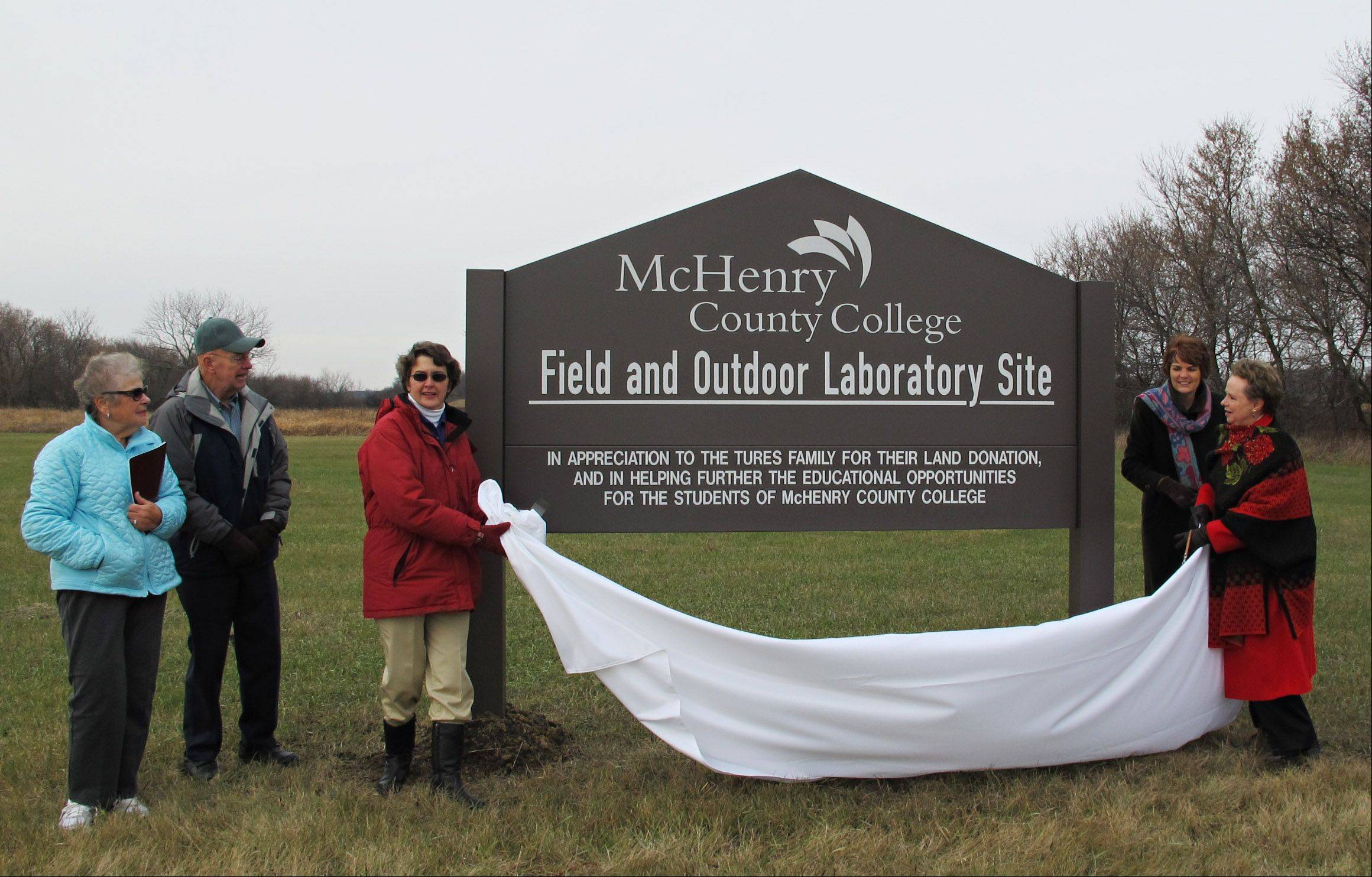Margaret and John Tures of Huntley watch as McHenry County College officials unveil a sign on Wednesday during a dedication ceremony for a 9.7-acre parcel of land in Chemung donated by the Tures family to the Friends of McHenry County College Foundation. Pictured are, from left, Margaret and John Tures, biology instructor Bev Dow, executive dean of math, sciences and health professions Amy Maxeiner, and MCC President Vicky Smith.