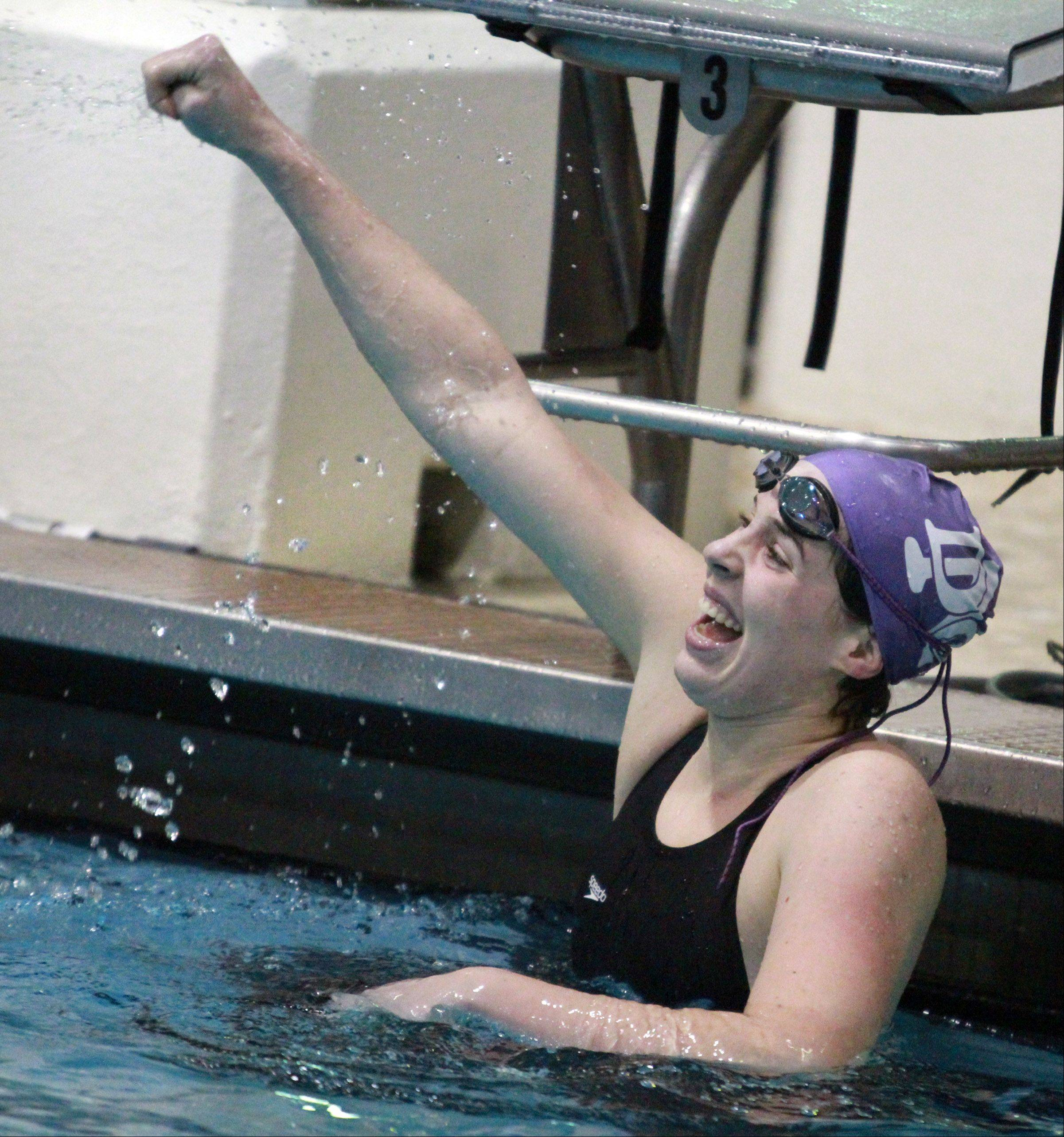 Gabby Sims with Downers Grove North celebrates winning heat 10 and placed first in the 100-yard freestyle at state preliminaries in Evanston on Friday, November 15, 2012.