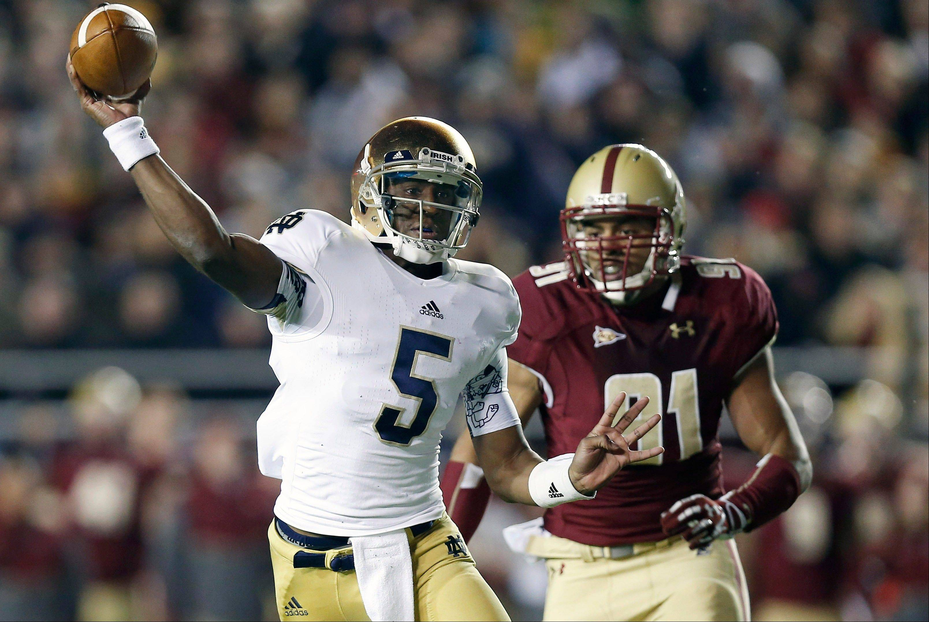 Notre Dame quarterback Everett Golson throws under pressure from Boston College's Kasim Edebali during the first half of an NCAA college football game in Boston Saturday, Nov. 10, 2012.