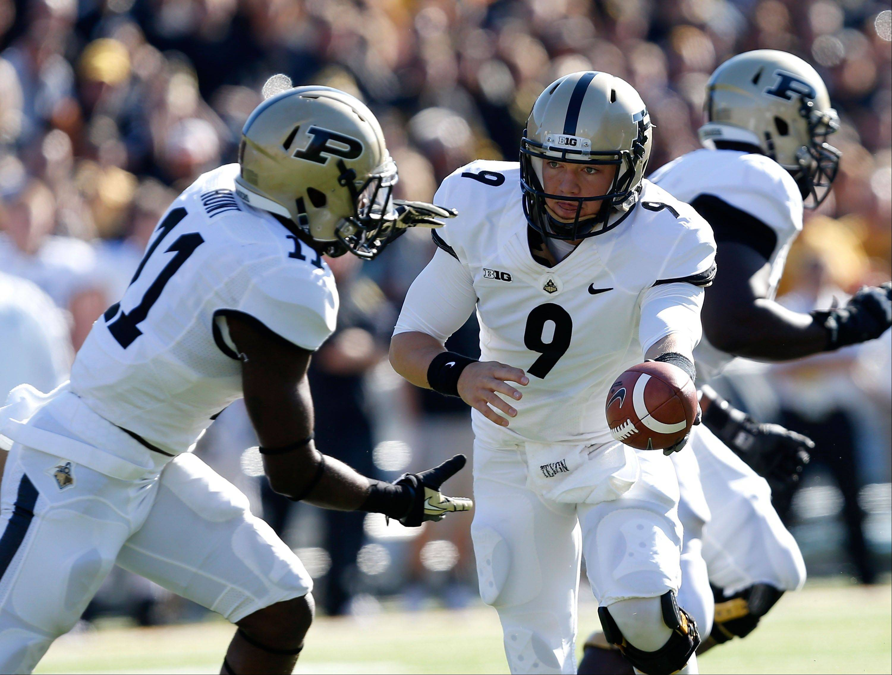 Purdue quarterback Robert Marve (9) hands the ball off to running back Akeem Hunt (11) during the first half against Iowa in an NCAA college football game Saturday, Nov. 10, 2012, in Iowa City, Iowa. Purdue won 27-24.