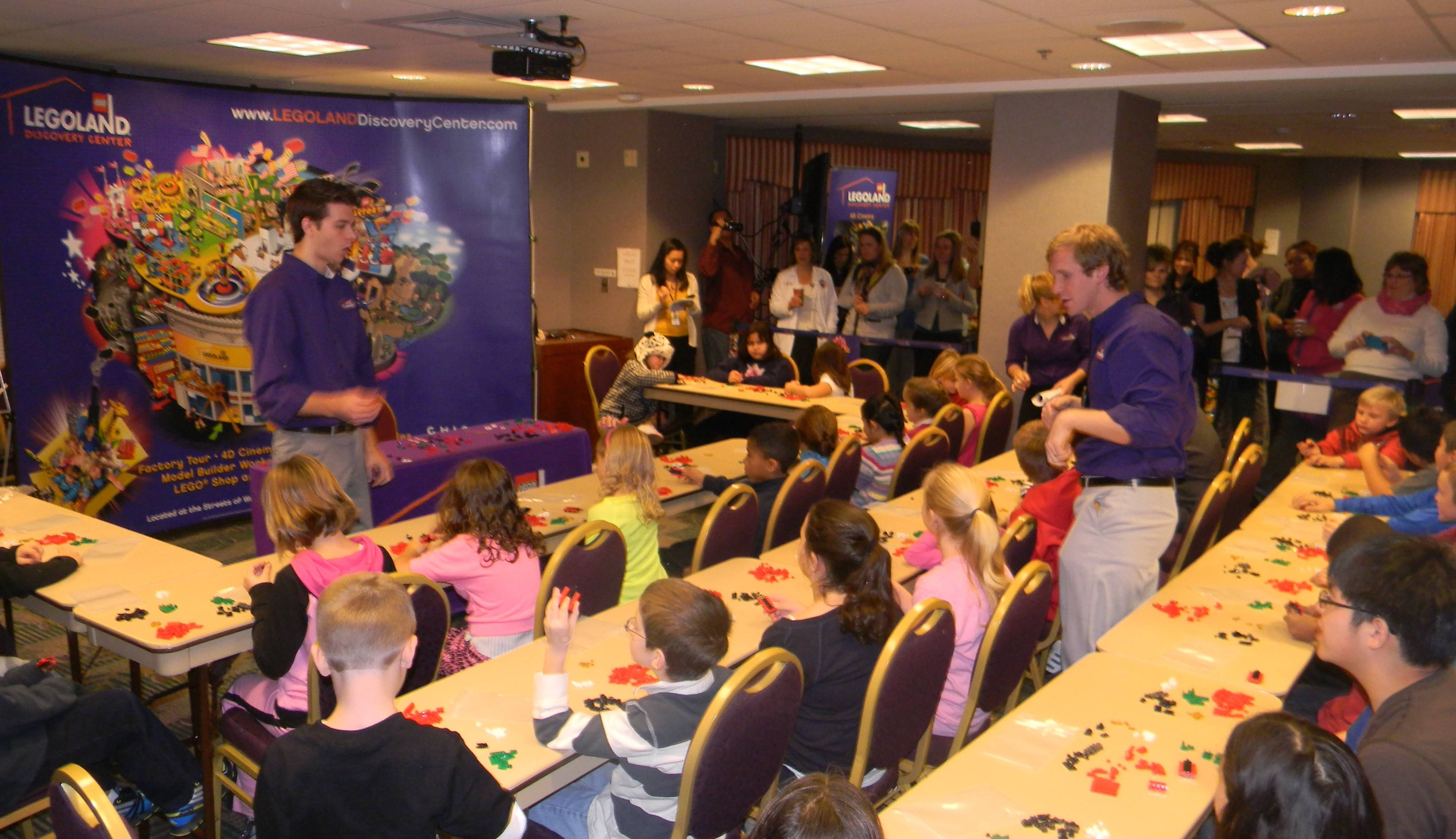 LEGOLAND Discovery Center Chicago's Andrew Johnson, left, and David Specha, right, successfully lead the model building workshop with children of the St. Alexius Medical Center community, achieving the Guinness World Record for the largest toy building lesson.