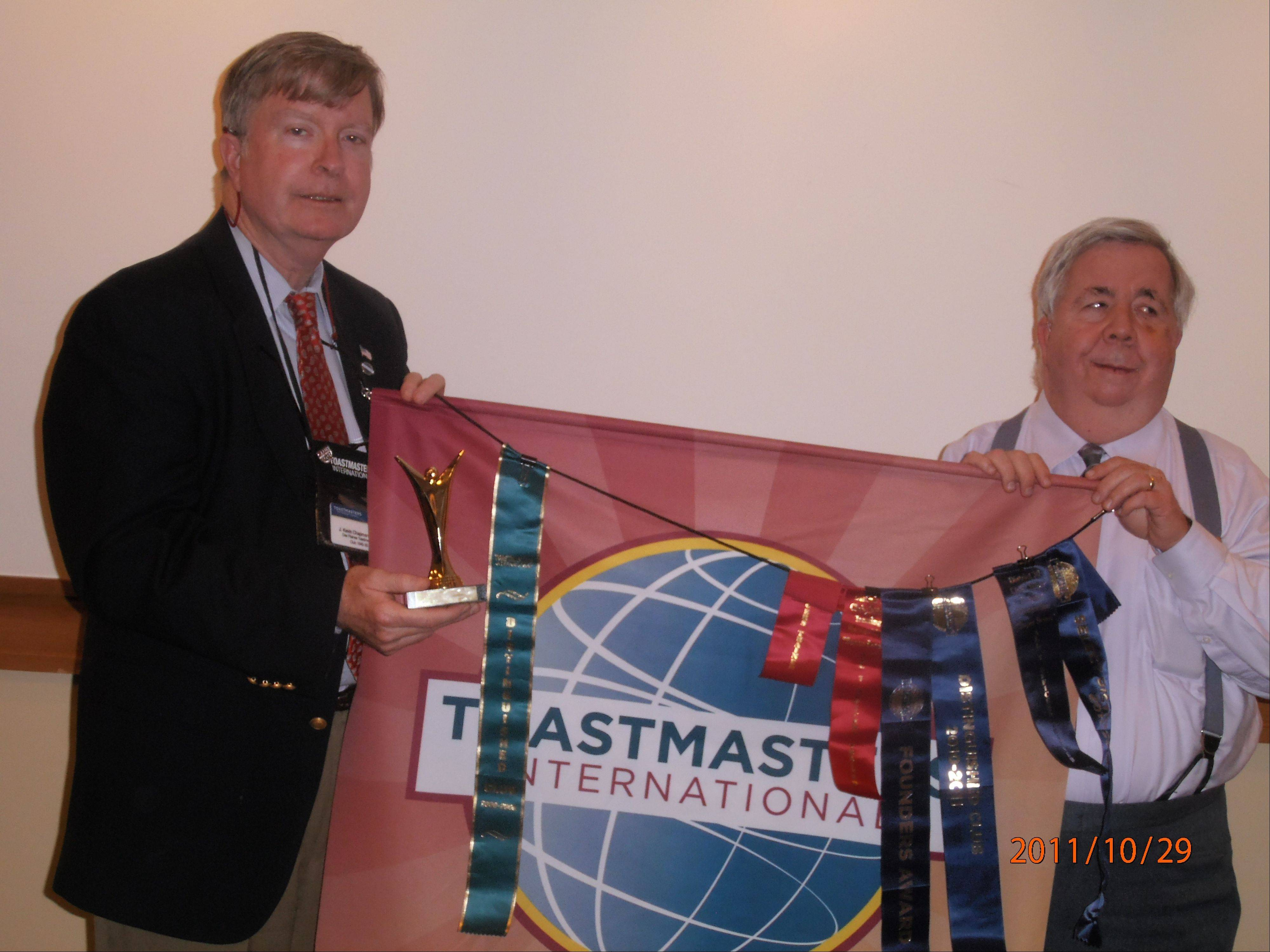 Kevin Chapman, left, president of the Des Plaines Toastmasters, holds the Select Distinguished Award trophy with club member Hap Holly of Des Plaines.